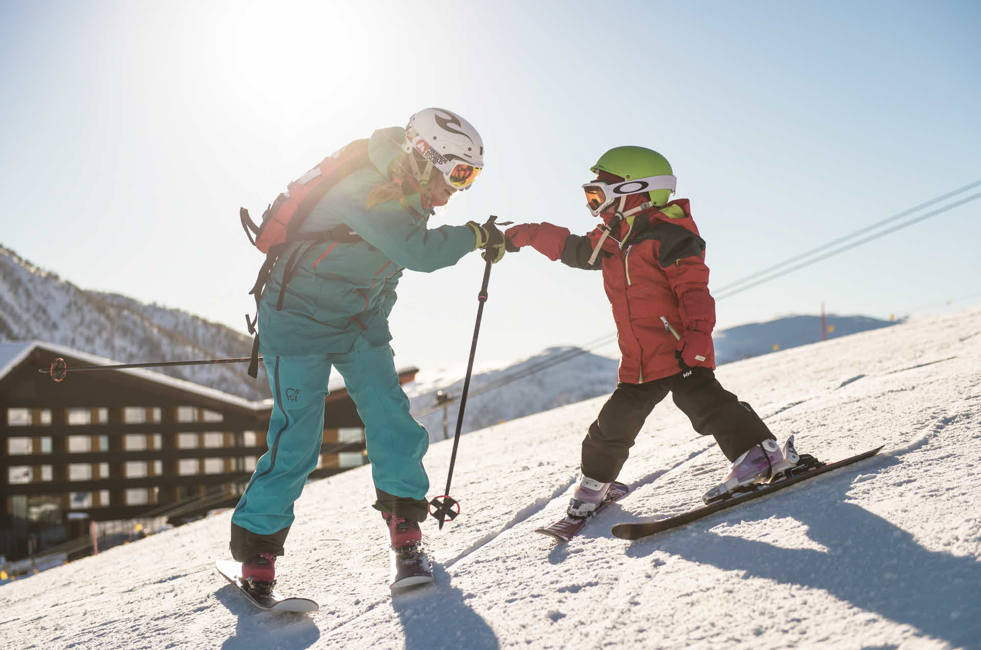 Et barn og en voksen på ski foran Myrkdalen Hotel