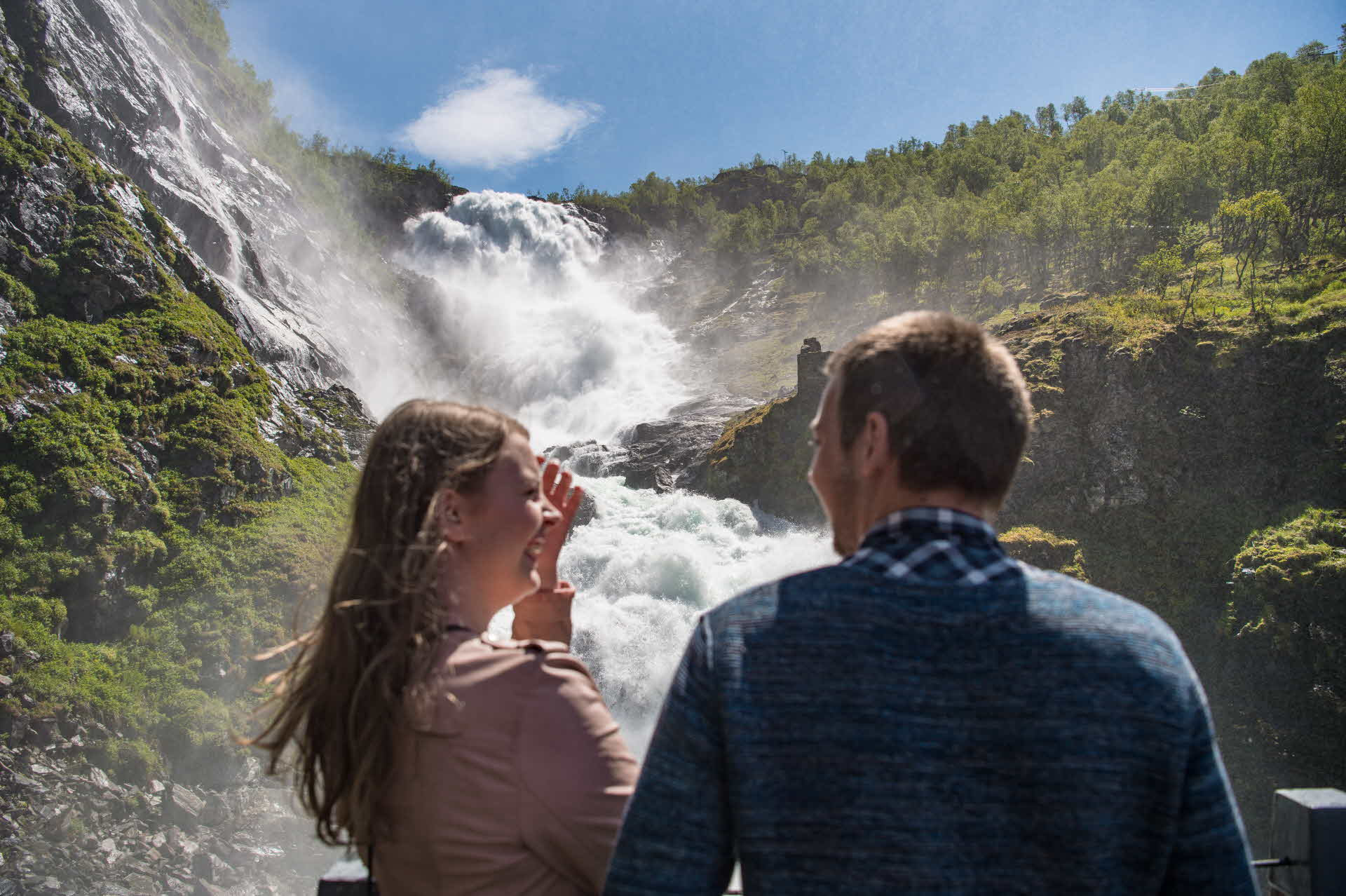 A woman and a man smile at one another in front of Kjosfossen