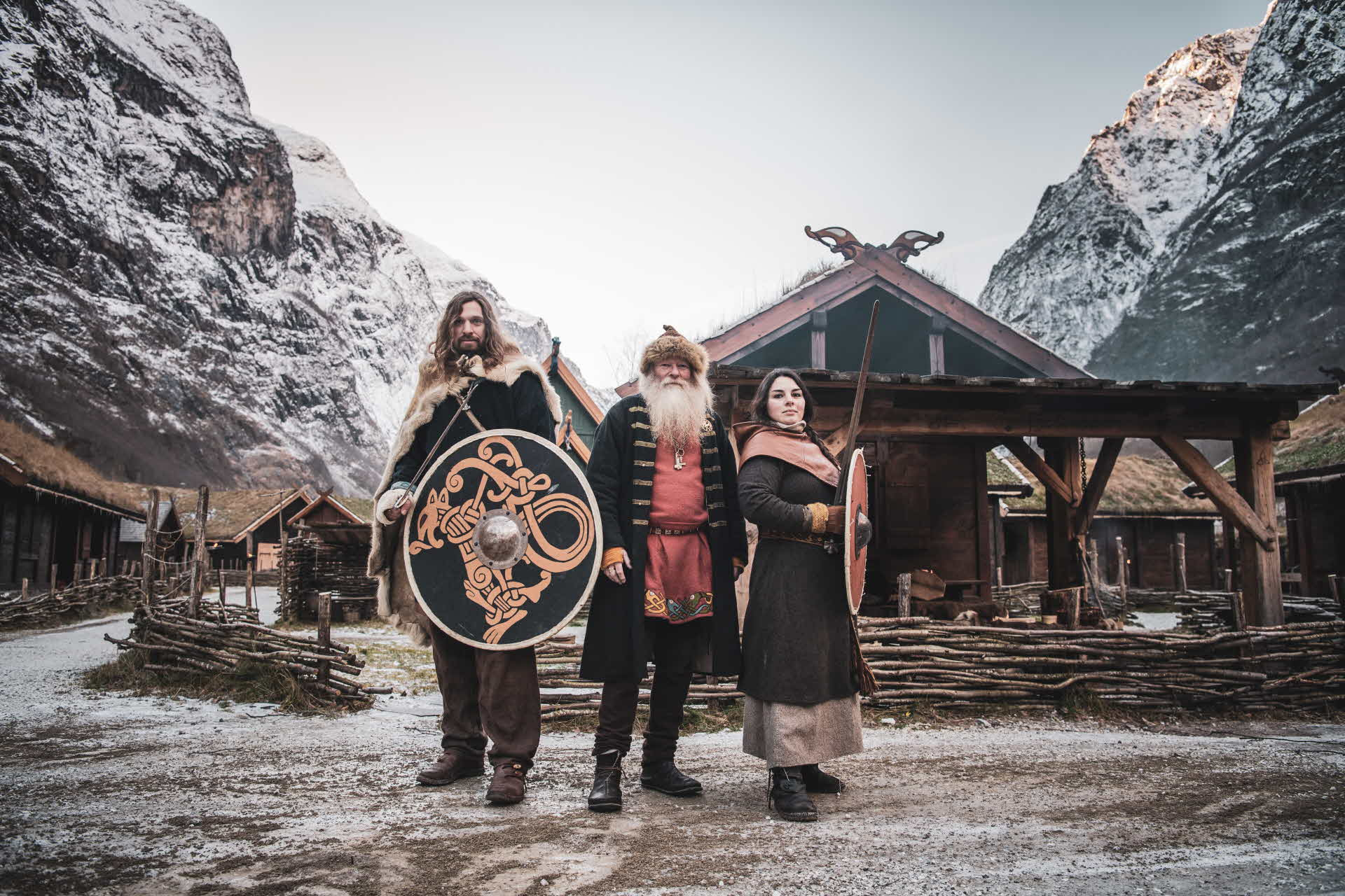 3 'authentic' Vikings standing in front of chief's house in Viking Valley Gudvangen on crisp winters day surrounded by high mountains