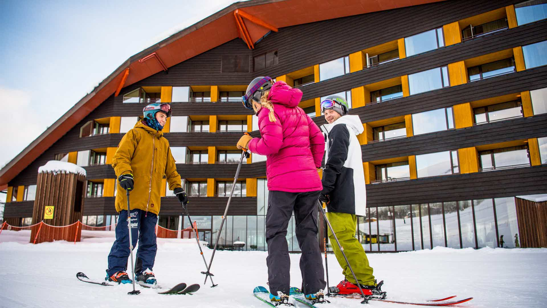Three people on skis standing by the slopes outside Myrkdalen Hotel