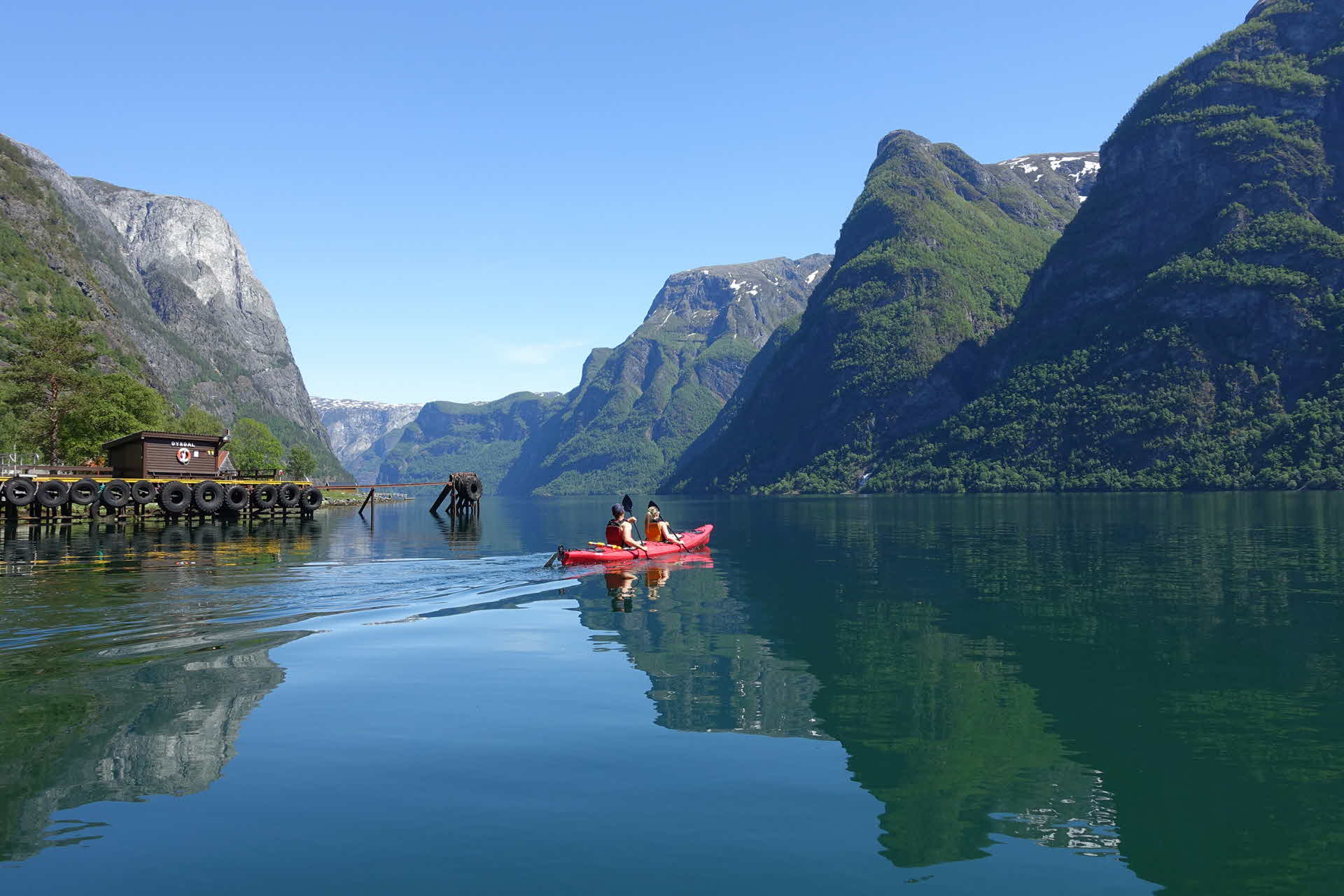 A couple paddle in red kayak on calm sea summer day in Naeroyfjord from Dyrdal lush steep mountains drops