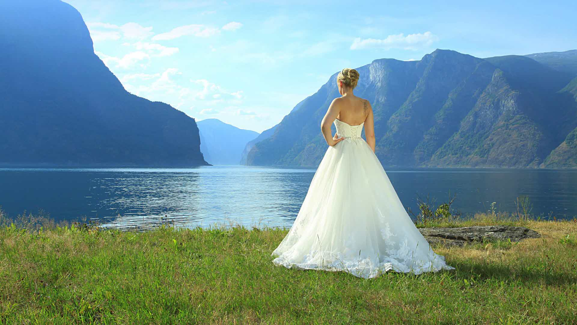 A woman in a long, white wedding dress seen from behind looking out on the Aurlandsfjord.