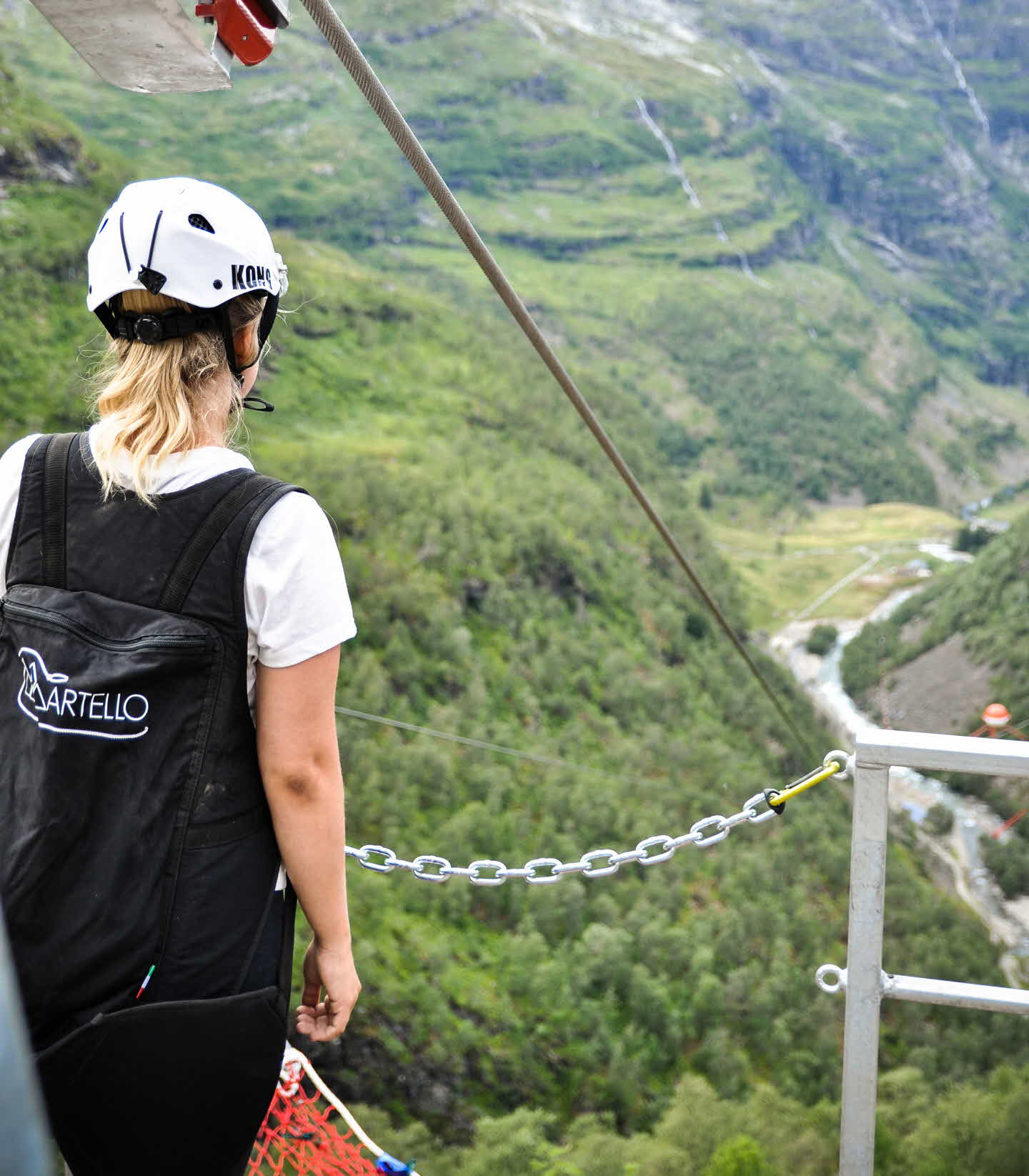 Woman in safety harness and helmet overlooking Flam valley from Flåm Zipline starting platform