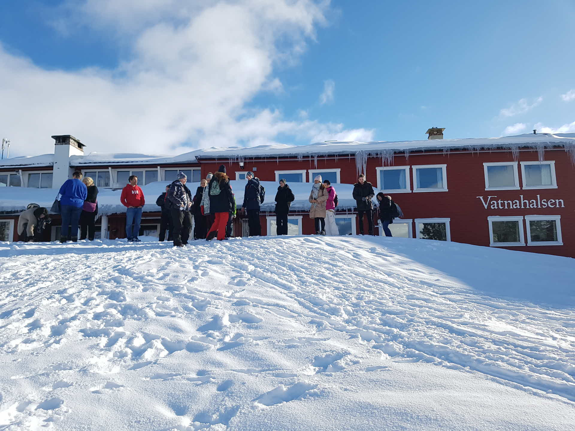 Group of people in winter clothing in front of Vatnahalsen Hotel on a sunny winter day. Long Icicle hanging from roof.