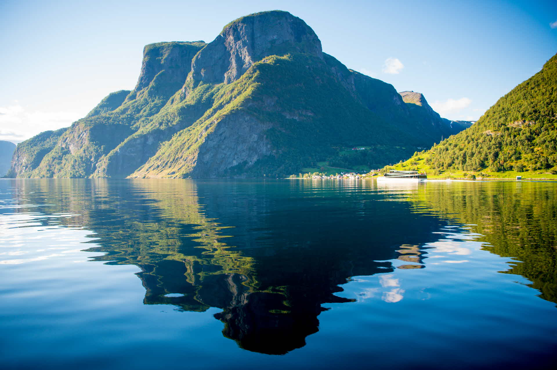 Steep mountains in Naeroyfjord mirror themselves on a summer day as Vision of The Fjords are sailing in the distance
