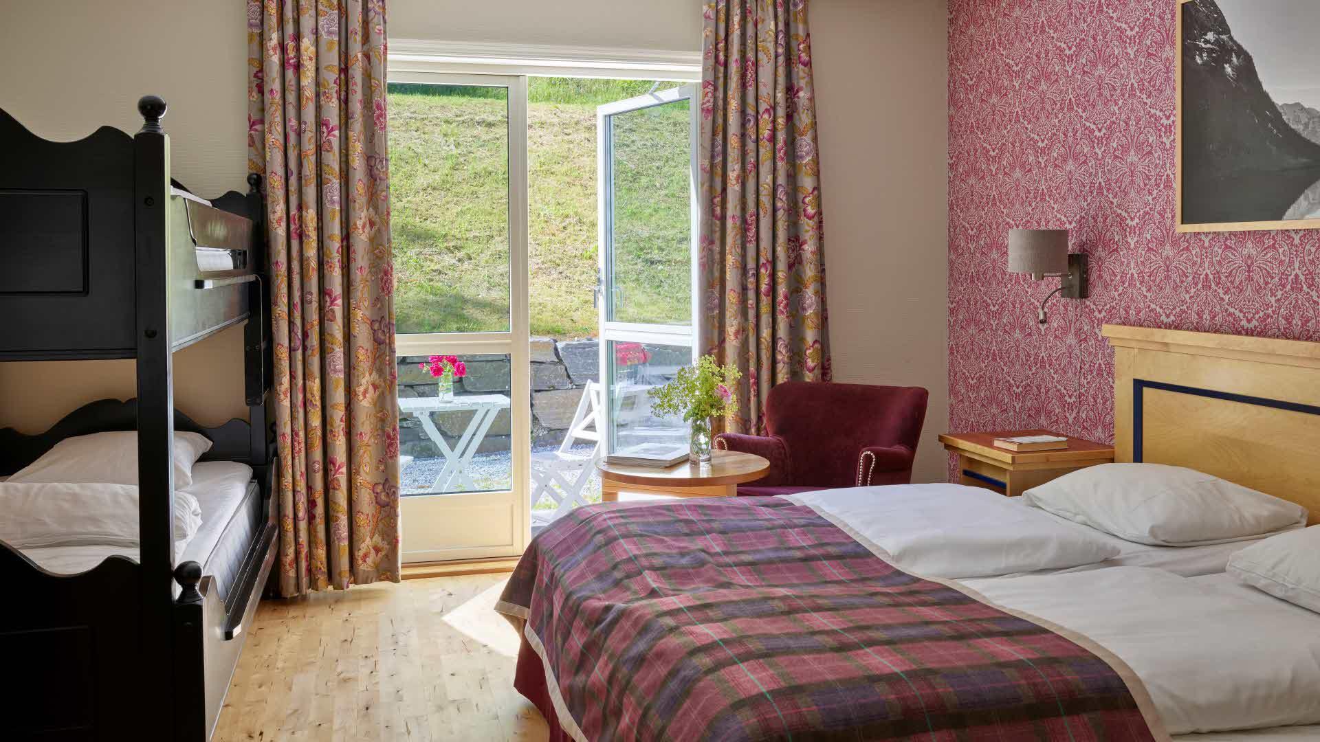 Et av Fretheim Hotels to familierom, med to enkeltsenger satt sammen og køyeseng i full lengde. Sitteplasser både inne og utenfor.