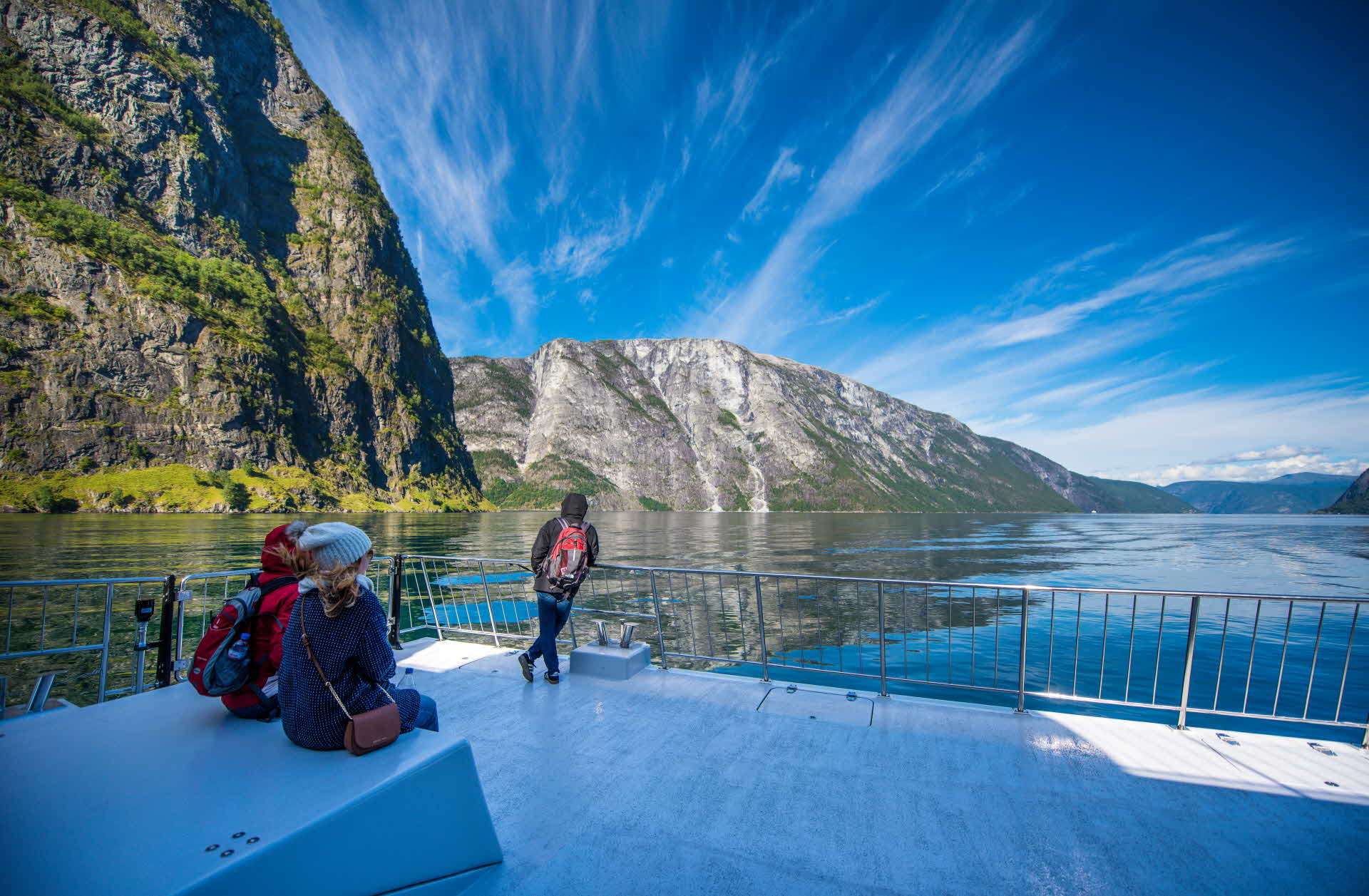 3 people are enjoying the spectacular view from front deck of Future of The Fjords as sailing UNESCO Naroyfjord summer
