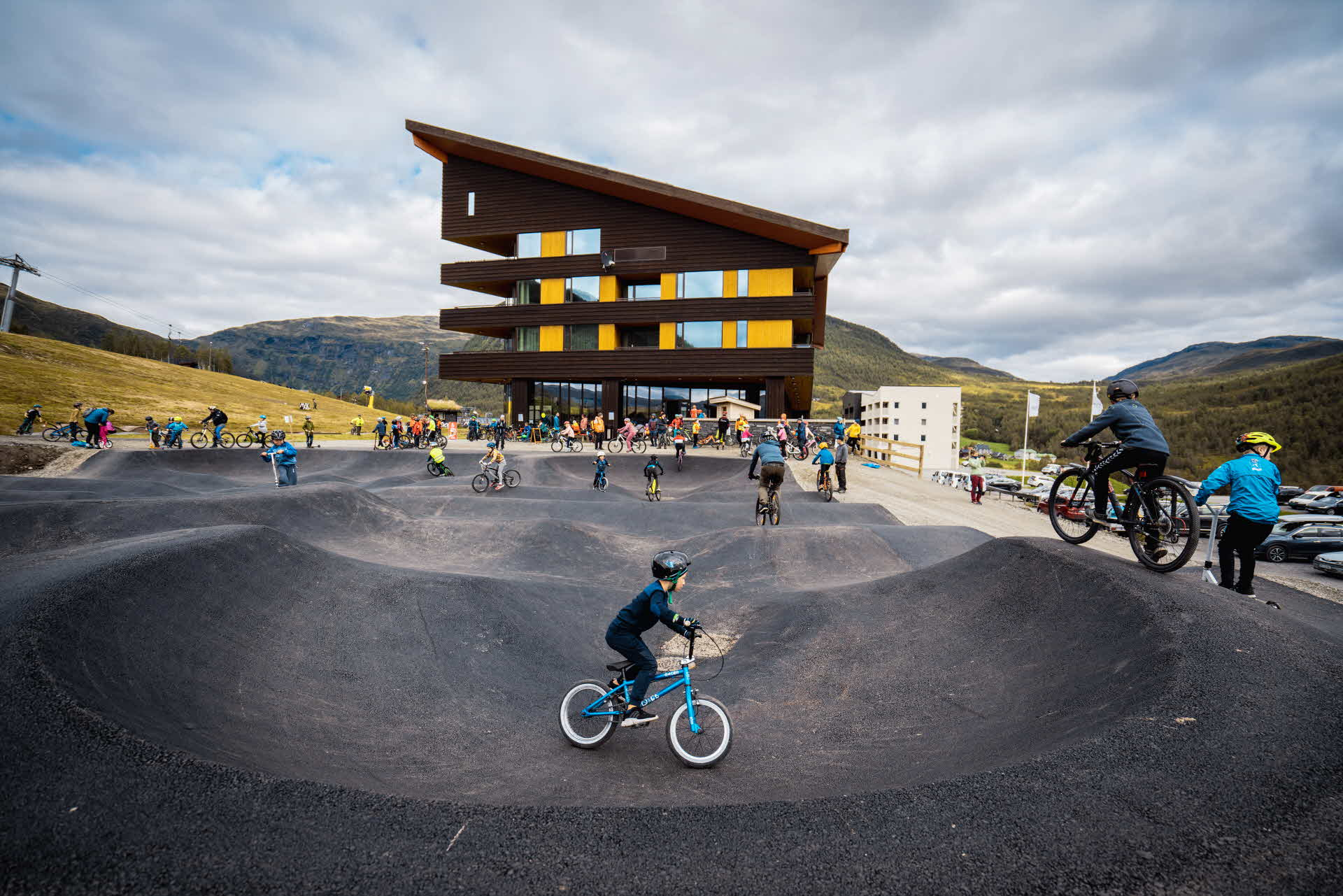 Children and adults cycle on the pumptrack outside the Myrkdalen Hotel