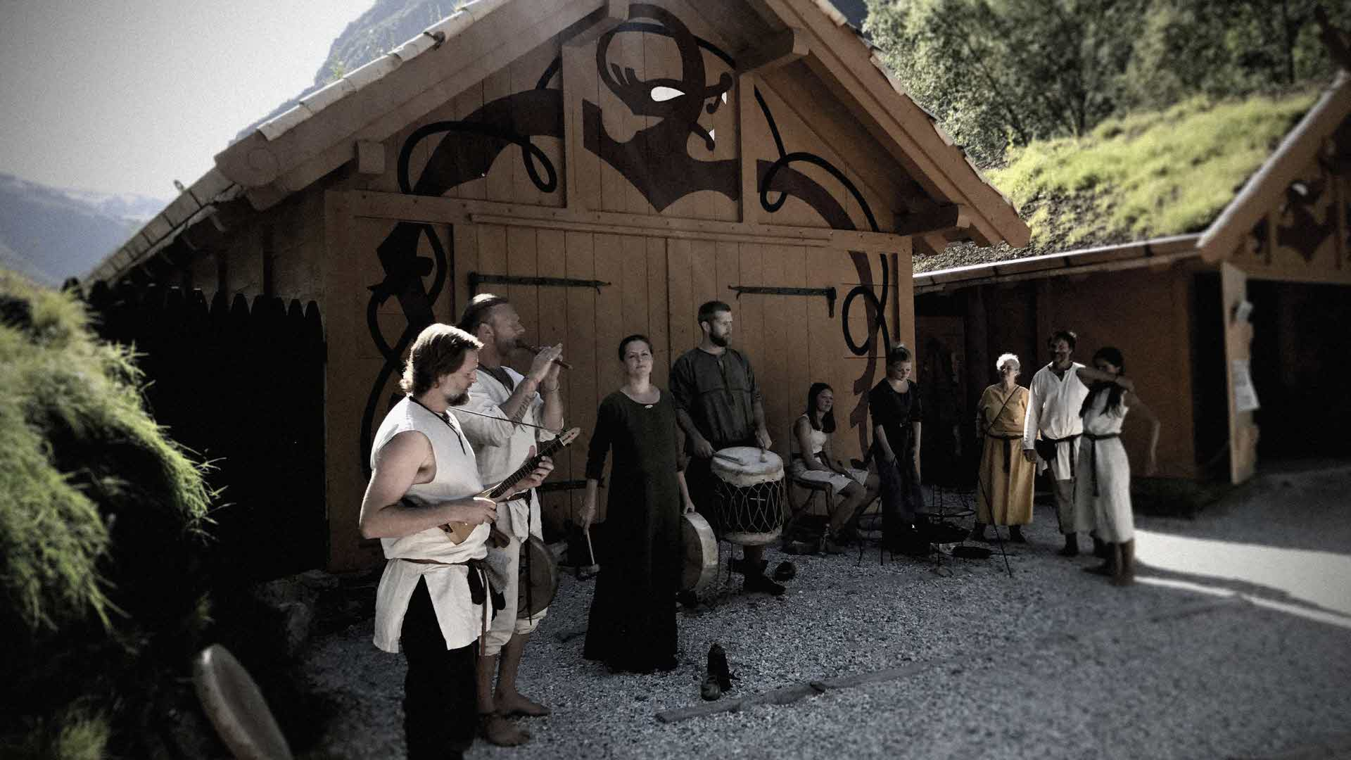 Vikingar i tidsriktige klær spelar og syng ved inngangen til Vikingbyen framfor autentiske bygningar