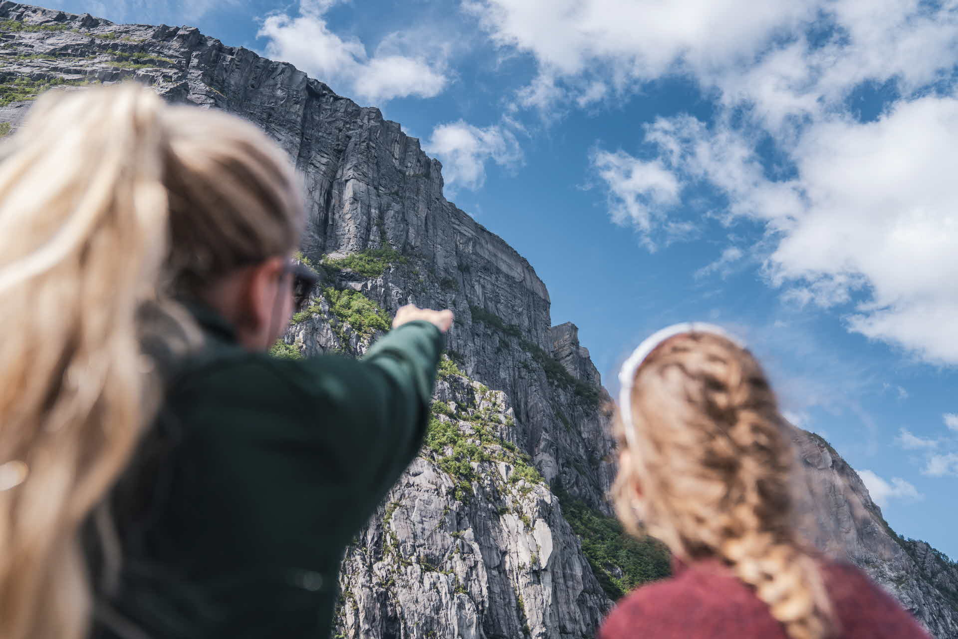 Woman pointing at Pulpit Rock from Fjord Cruise Lysefjord in Stavanger region next to girlfriend partly cloudy summers day