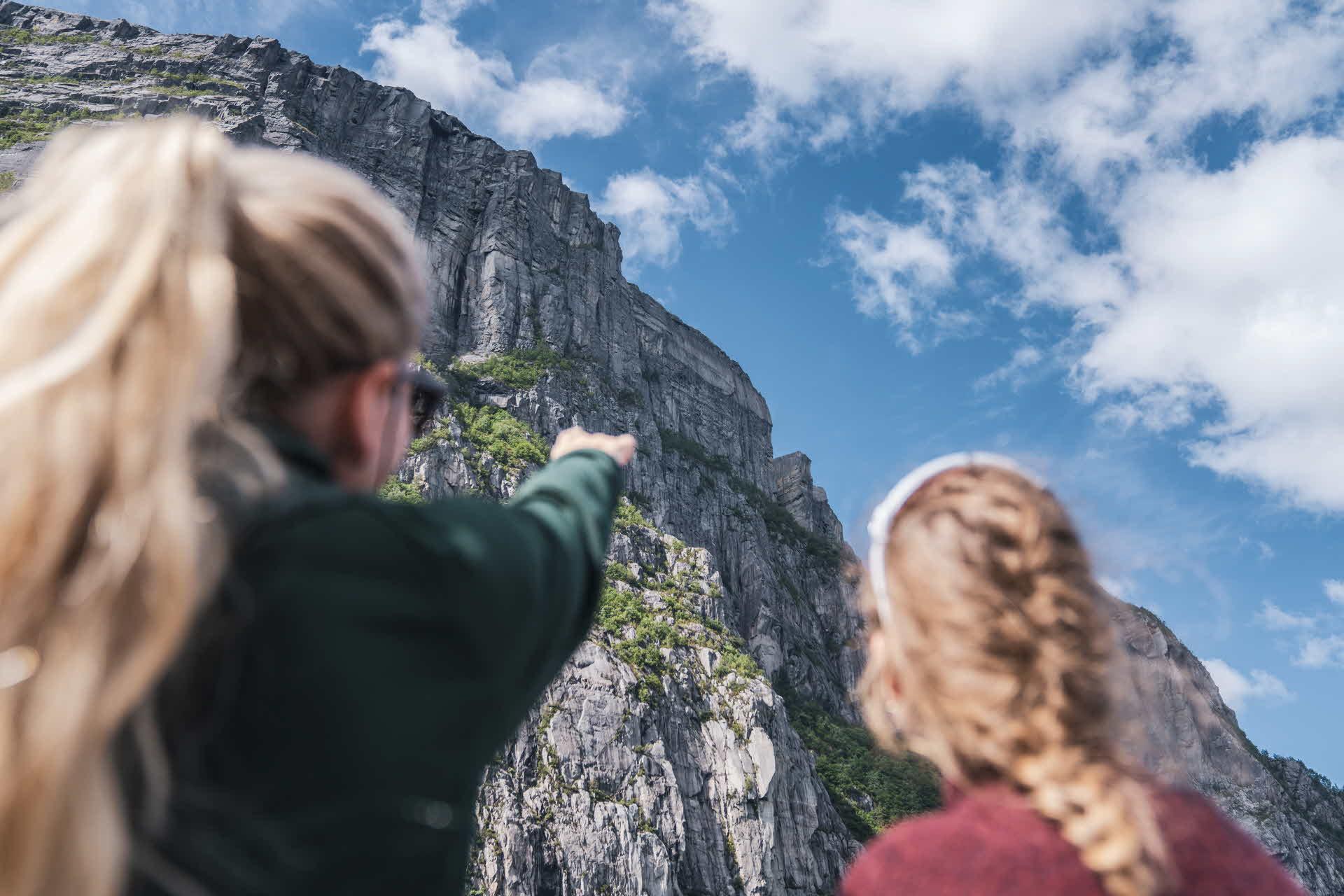 Kvinne peker mot Preikestolen om bord Fjord Cruise Lysefjord ved siden av venninne på en delvis overskyet sommerdag
