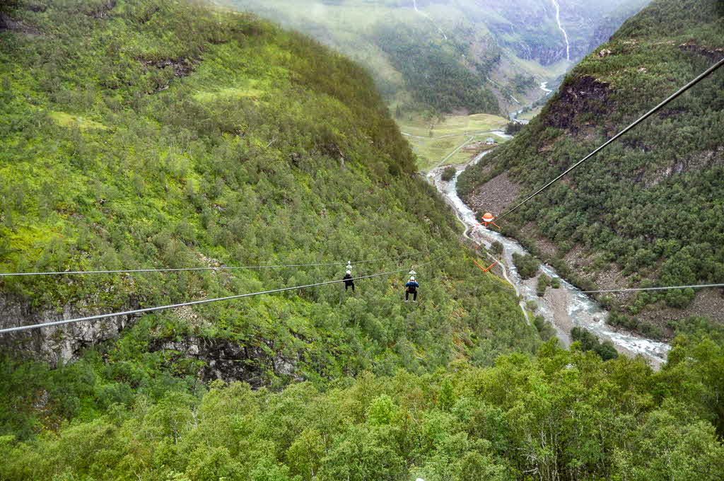 Two people hanging from the Flåm Zipline on their way down towards Flåmsdalen
