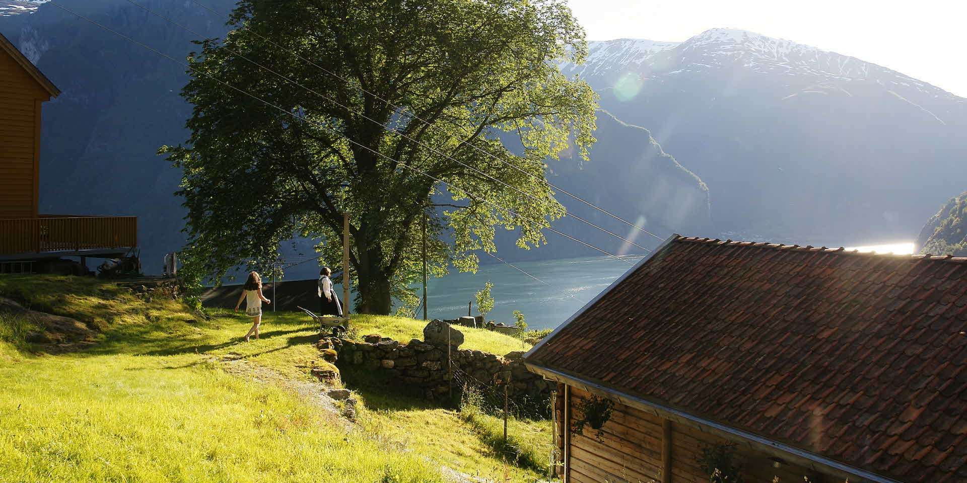 暖かい夏の日に、古い農場の建物の間に生えた草の上を歩く女性と子供。アウルランドスフィヨルドの素晴らしい眺め