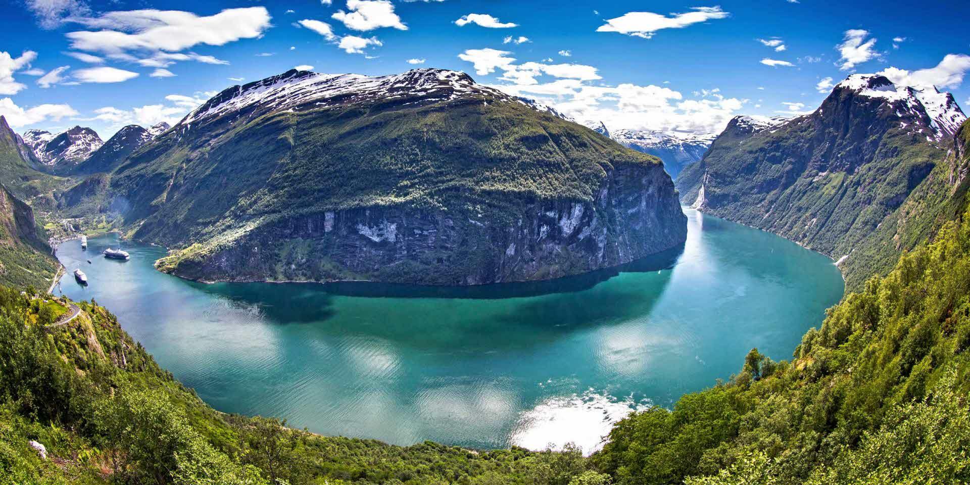 Panormabilde av Geirangerfjorden med mintgrønn fjord, frodige daler og fjellsider med snødekte topper