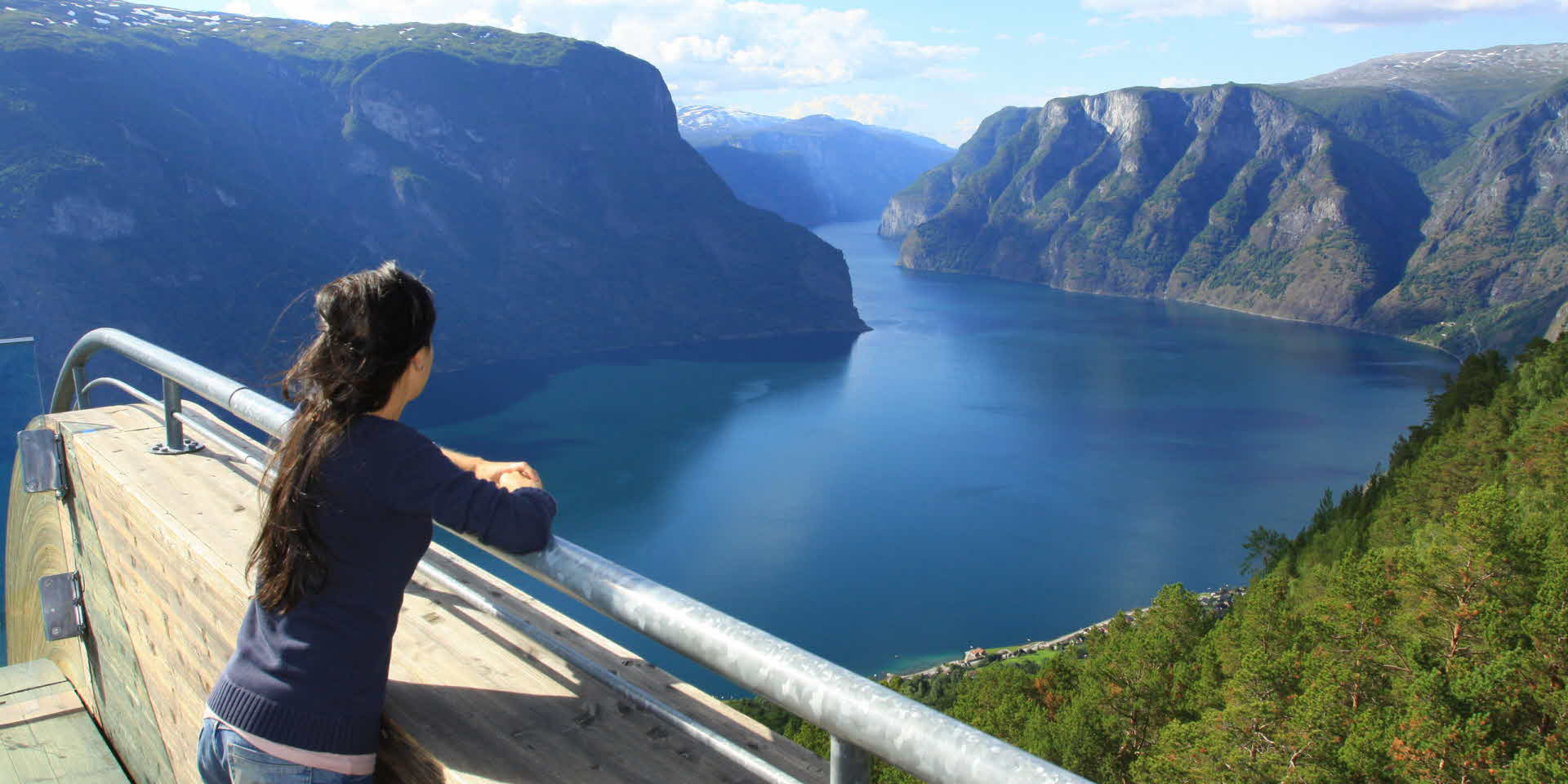 Woman standing on Stegastein Viewpoint platform in summer overlooking Aurlandsfjord