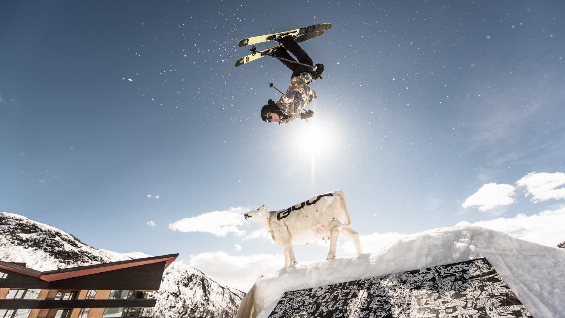 Man in alpine downhill gear doing front flip over a white cow statue in Myrkdalen Ski Resort on a sunny winter day