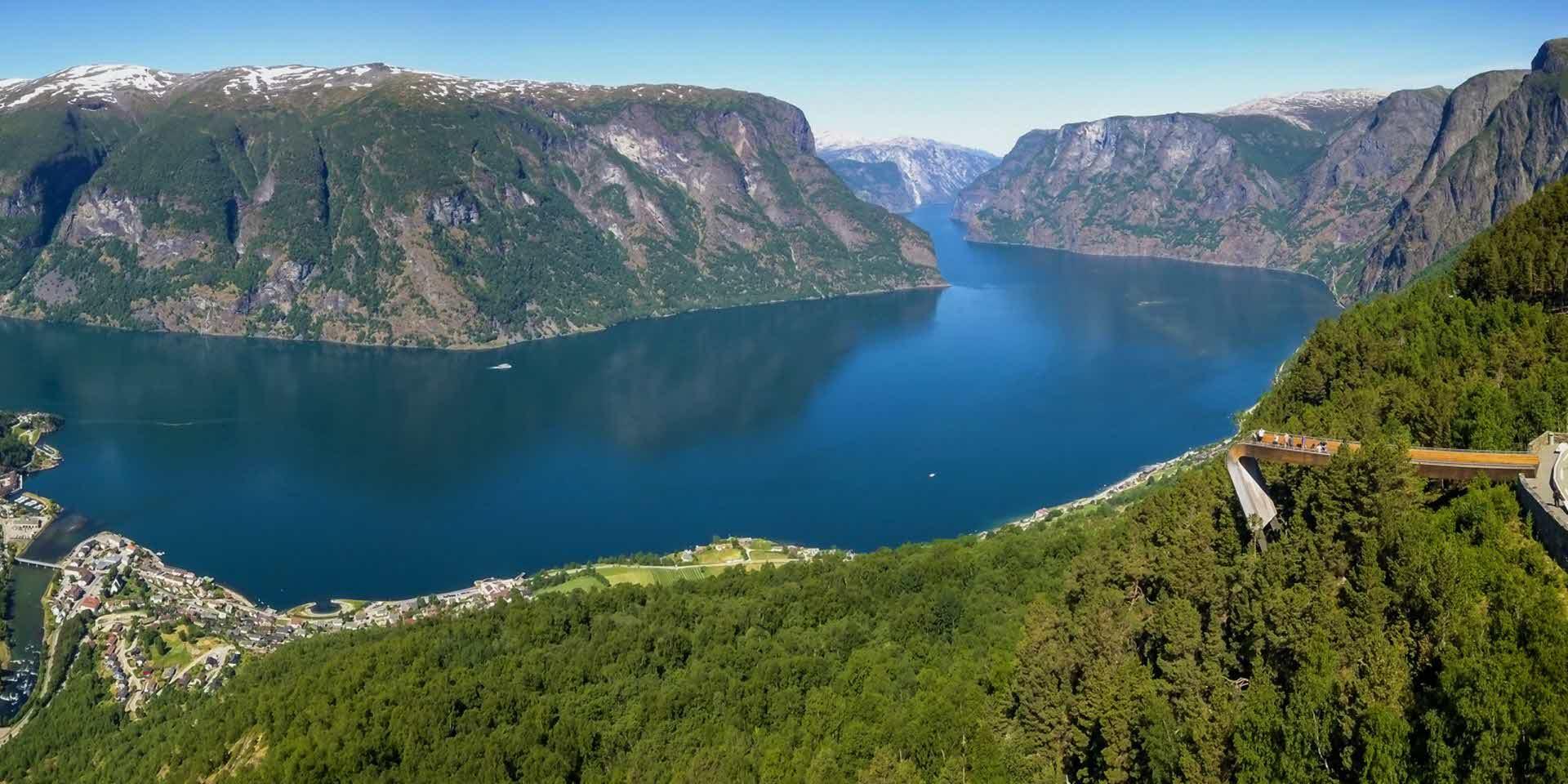Panorama av Aurlandsfjorden om sommaren. Stegastein utsiktspunkt sett ovanfrå og personar som ser utover den Unesco-verna fjorden