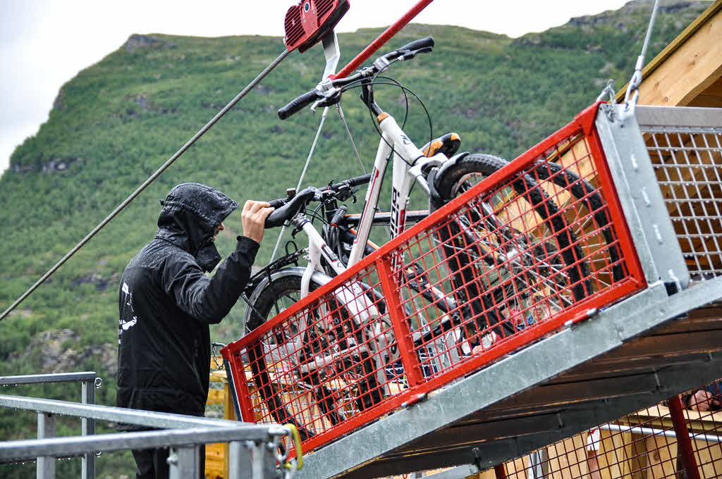 Bikes being loaded into cages at the Flåm Zipline on a rainy day