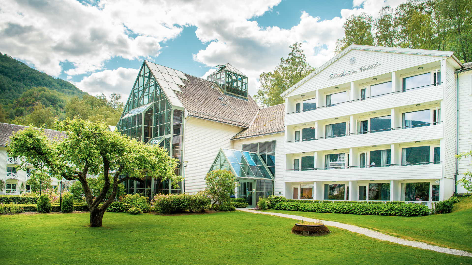 Fretheim Hotel, viewed from the garden on a partly cloudy summer day