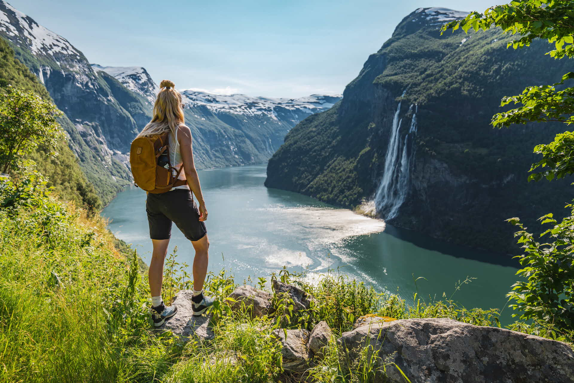 Woman standing on arock looking down to the Seven Sisters waterfall and Geirangerfjord
