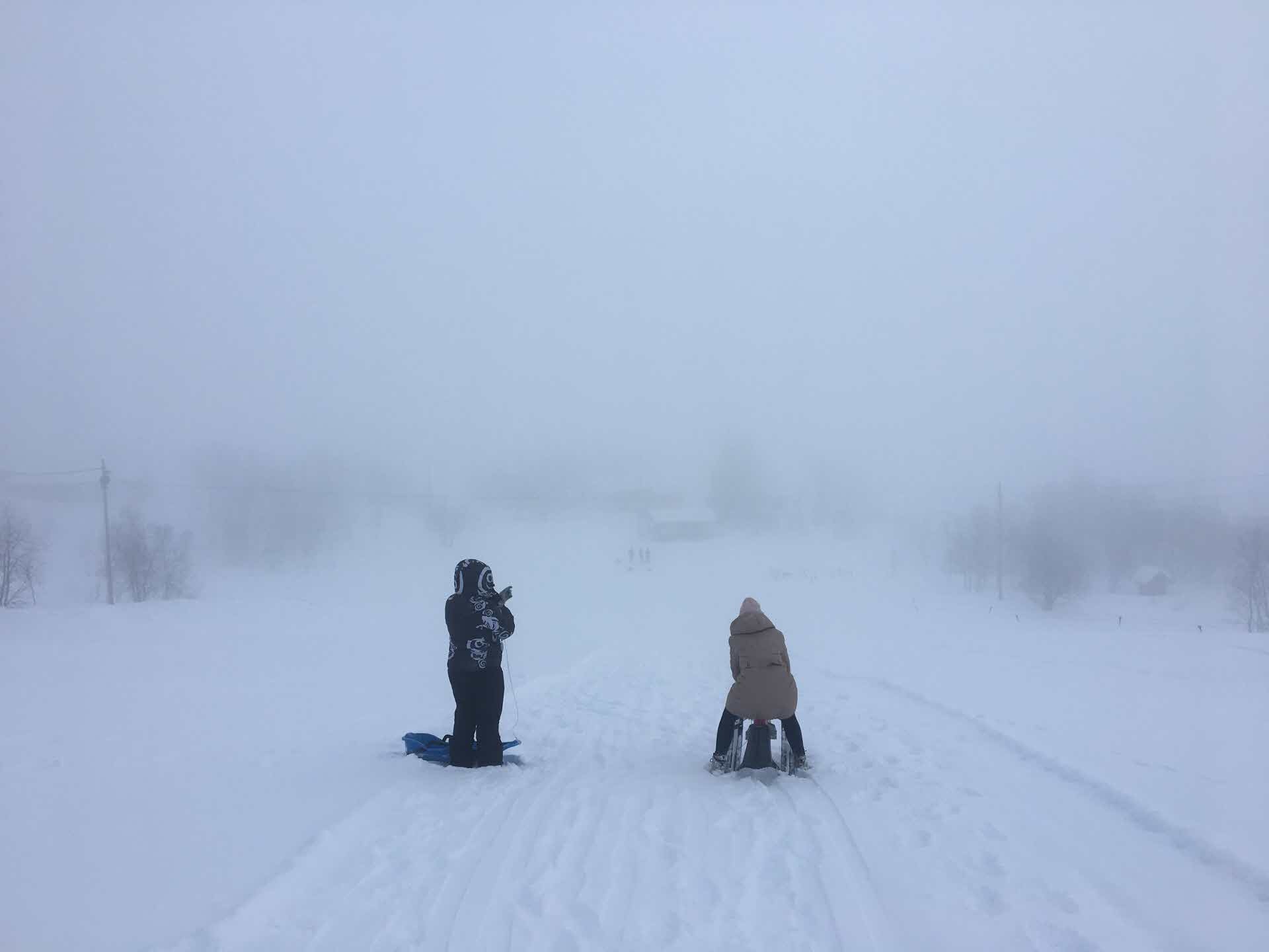 Two people getting ready for snow sleding on top of ski slope on a misty day