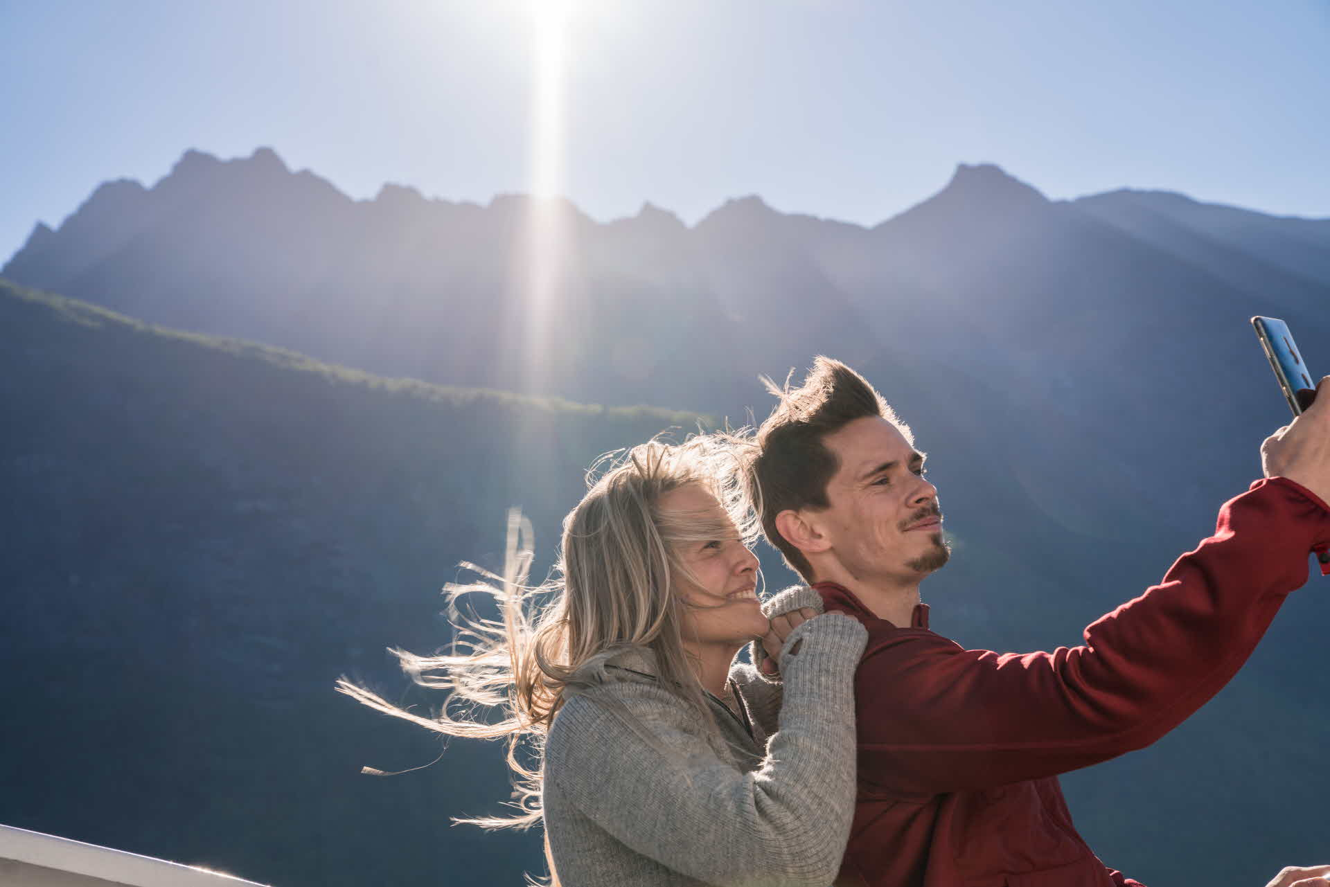 Young happy couple taking selfie onboard fjord cruise Hjorundfjord. Tall spiky wild mountains in background sunny day