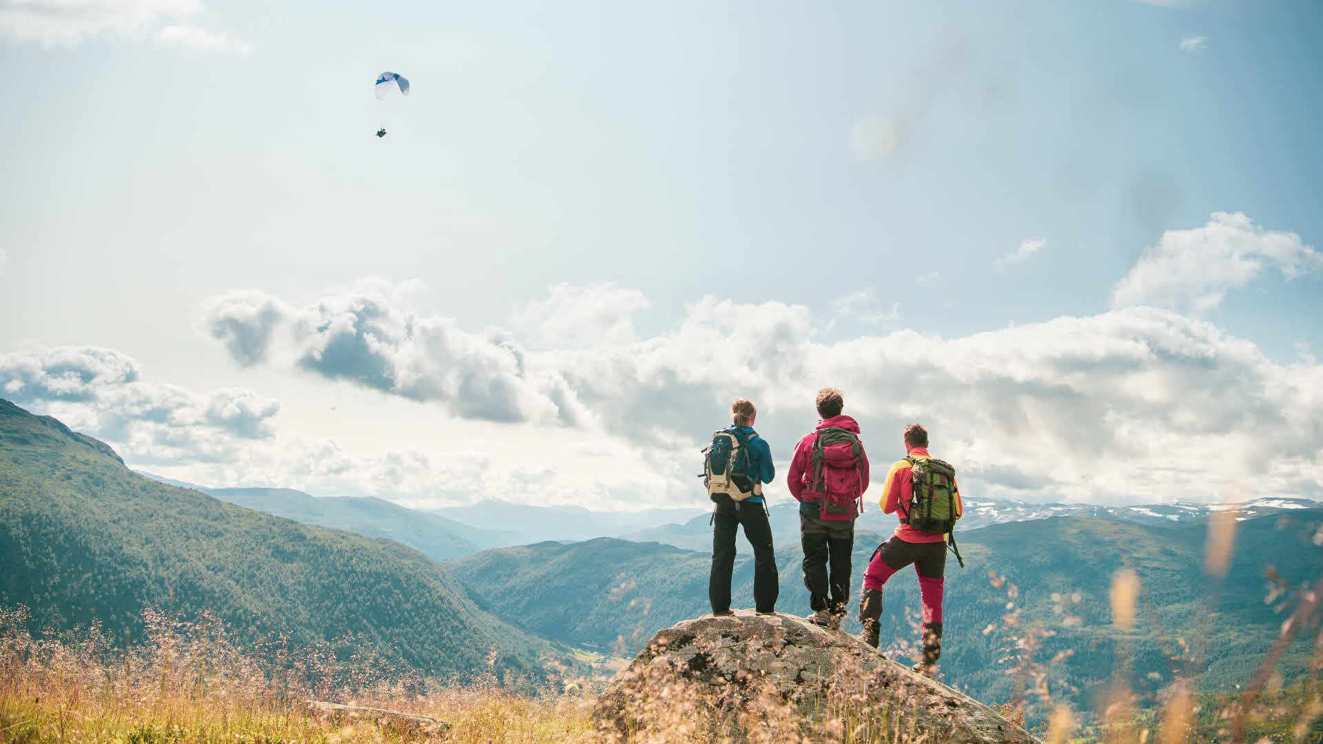 Three people standing on a rock and looking across Myrkdalen, with a paraglider flying over