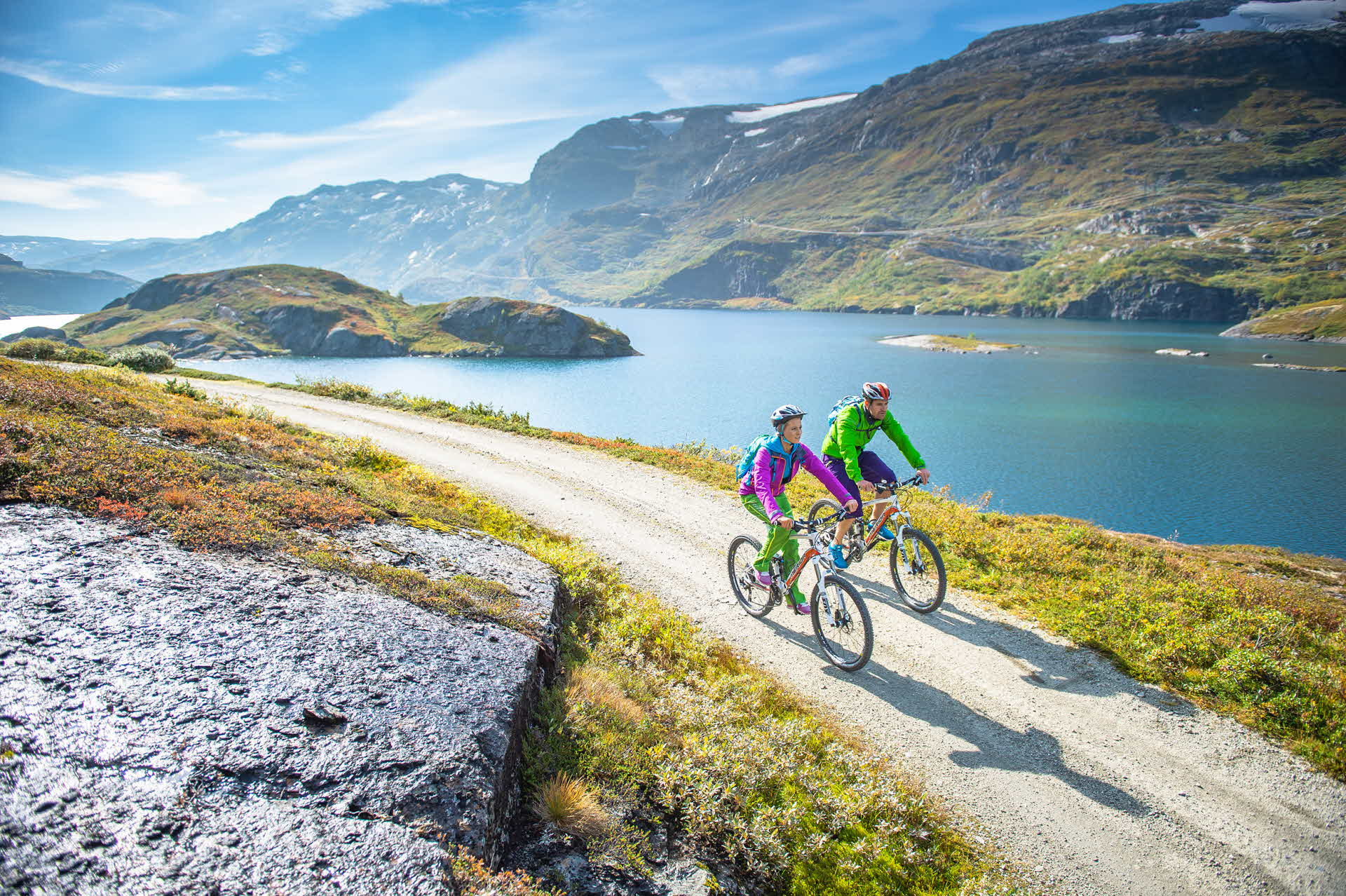 A man and woman cycling along a stream at Rallarvegen
