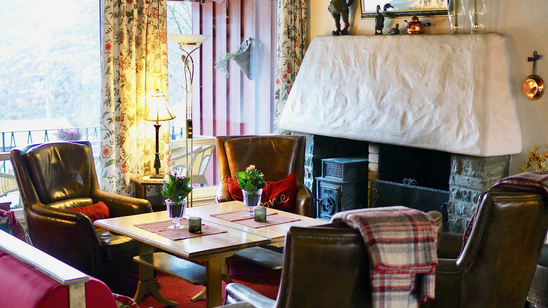 Inside Vatnahalsen Hotel in front of lit fireplace with classic leather chairs, flower curtains and old lamps