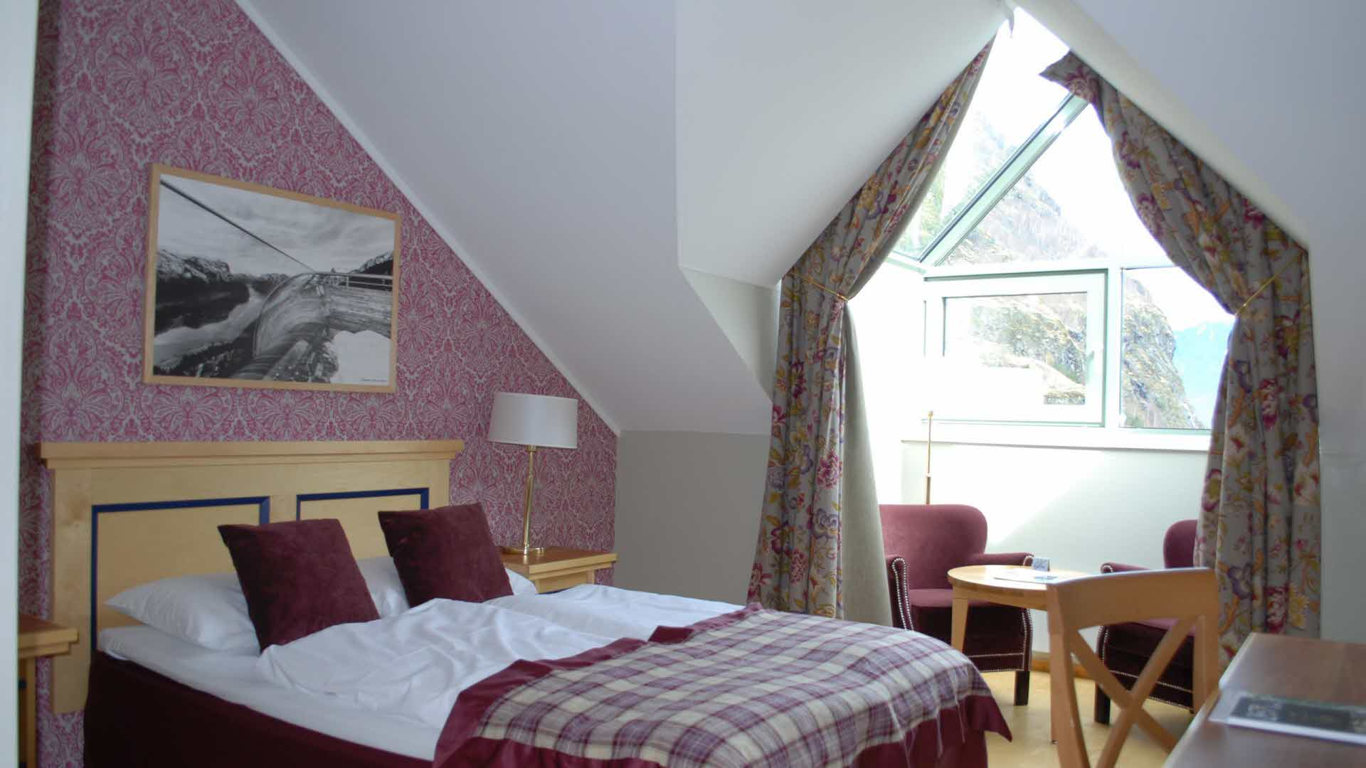 Single room at Fretheim Hotel made up for two people, with queen size bed in front and seating area in bay window in the back.