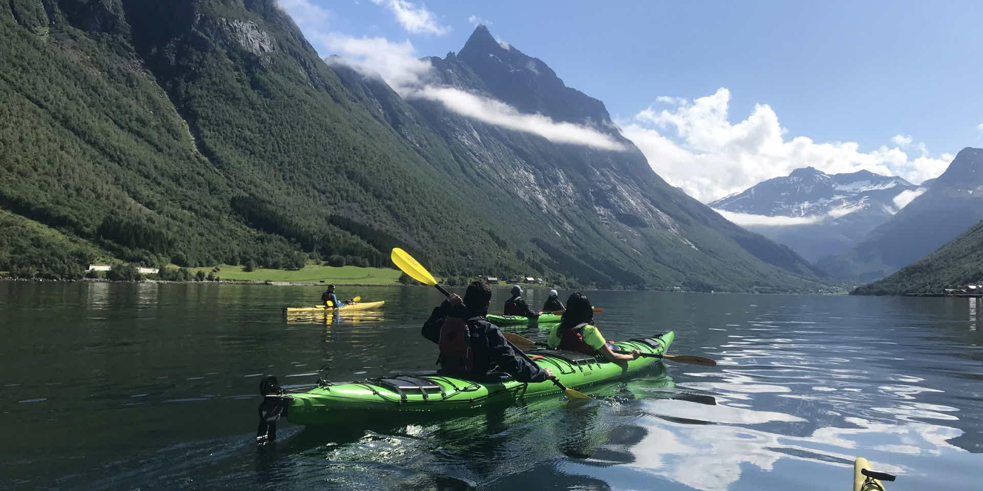 Personas haciendo kayak en Hjørundfjord, rodeados por un imponente paisaje de fiordos