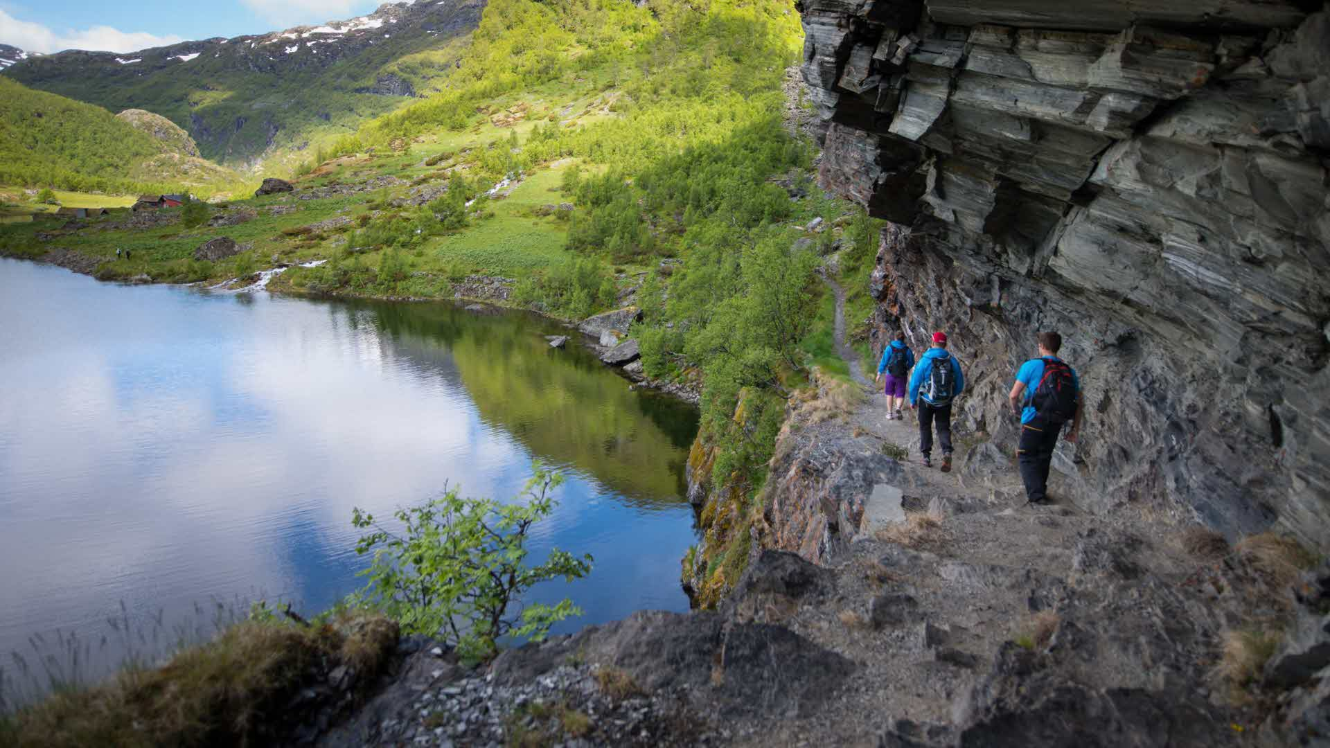 3 people hiking along steep and rocky ledge through Aurland valley with backdrop of lake