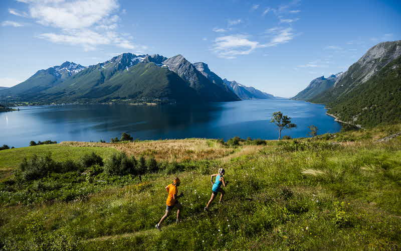 A man and a woman running on a trail above the Hjørundfjord