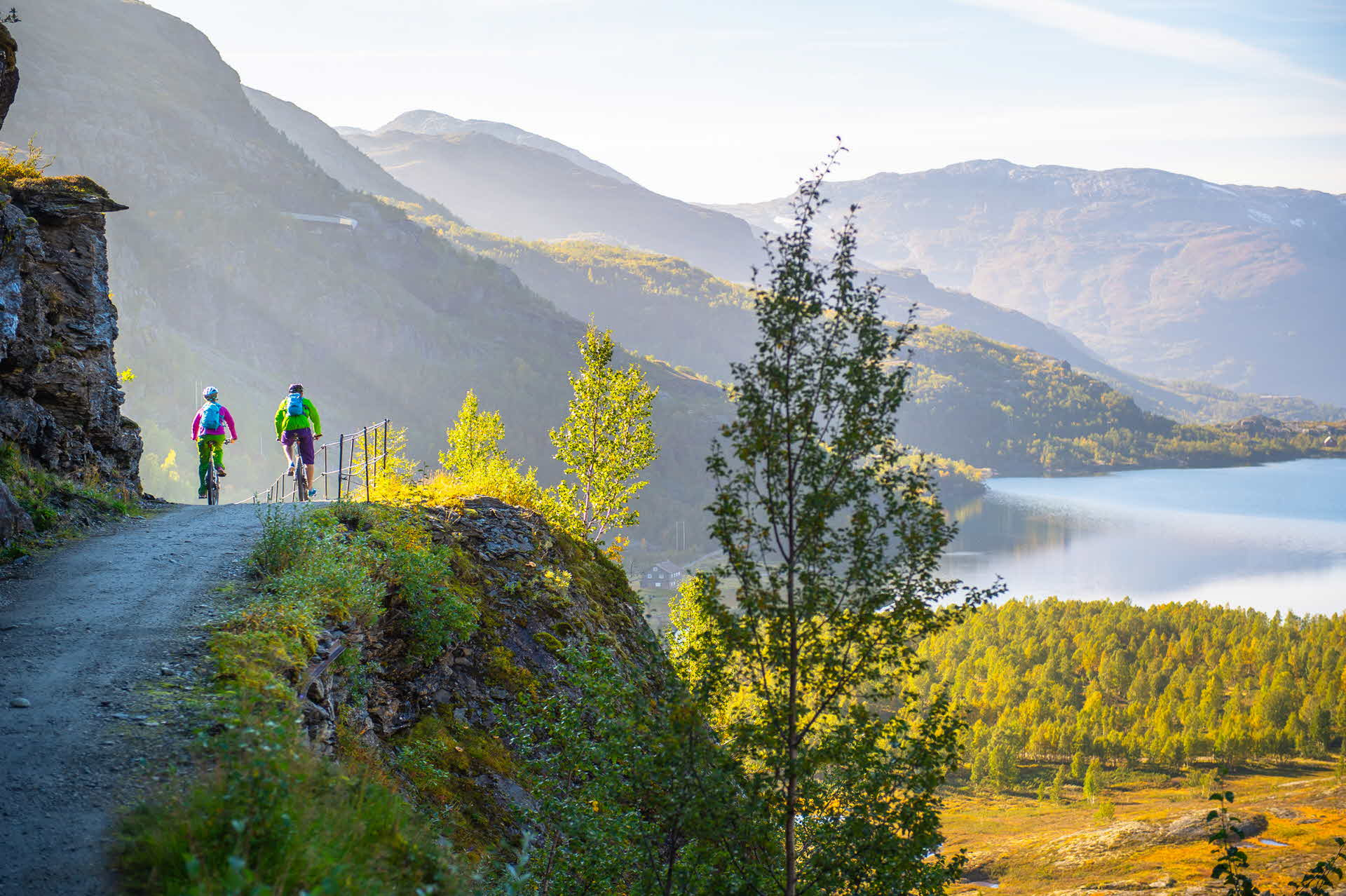 Two people cycling over a hill towards a stream on Rallarvegen