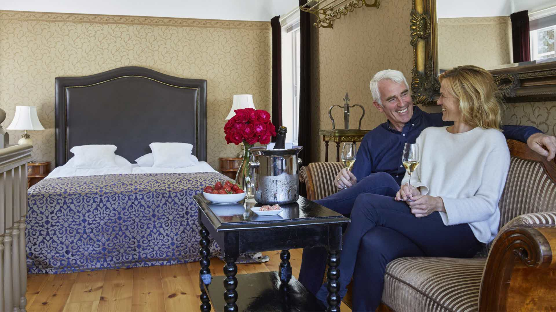 An adult couple relaxing in the historical tower suite's lounge, smiling while holding champagne glasses.