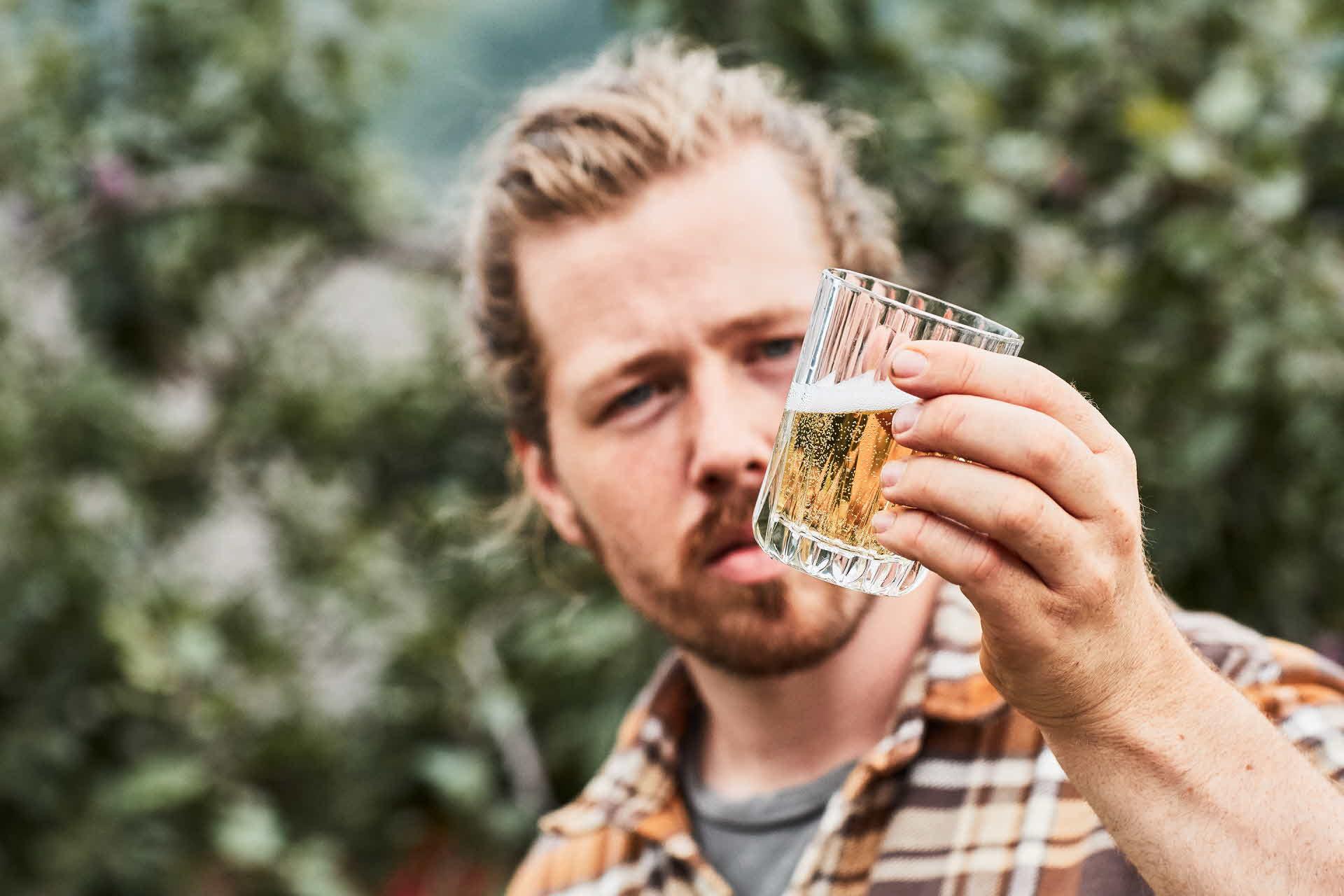 Ein Apfelbauer inspiziert frisch gezapften Apfelwein in einem Glas im Freien in Hardanger, Norwegen