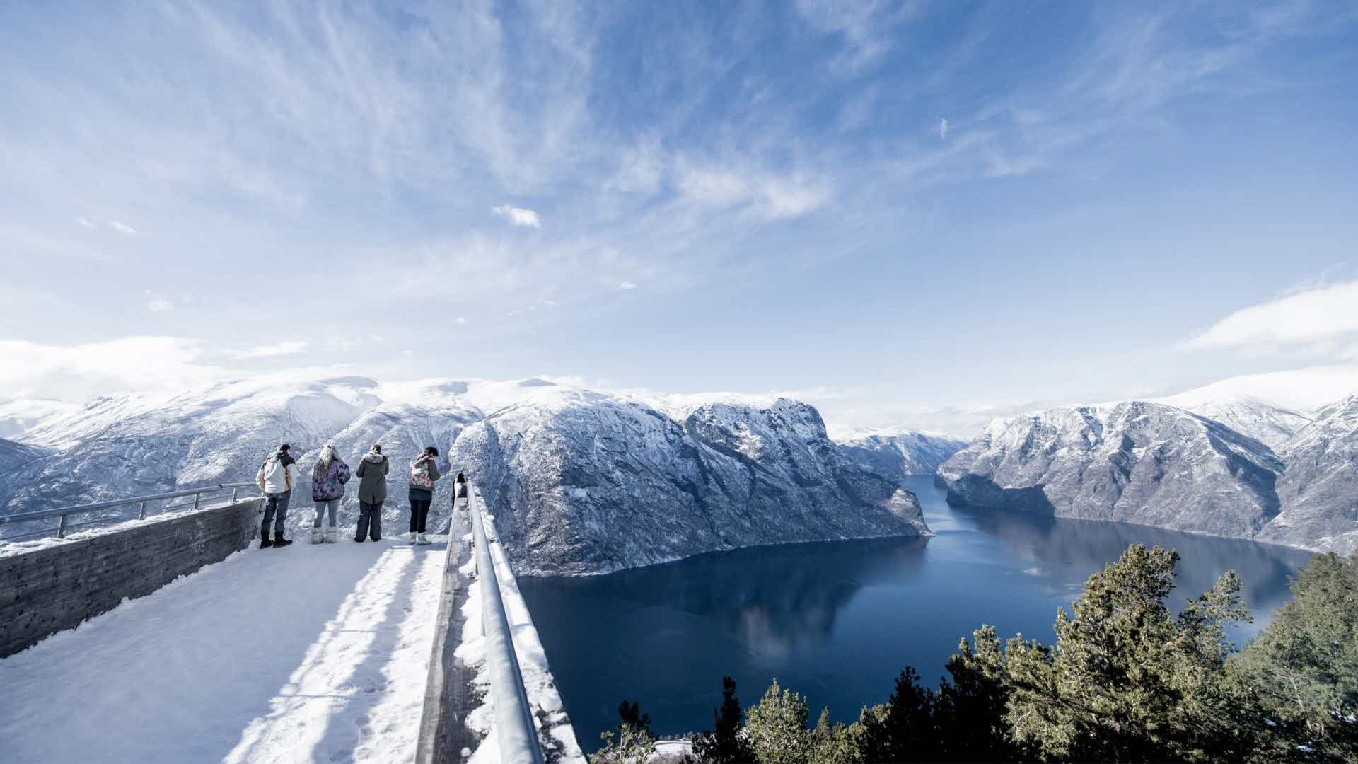 4 people standing on the Stegastein Viewpoint platform in sunny cold winters day, overlooking the mighty Aurlandfjord