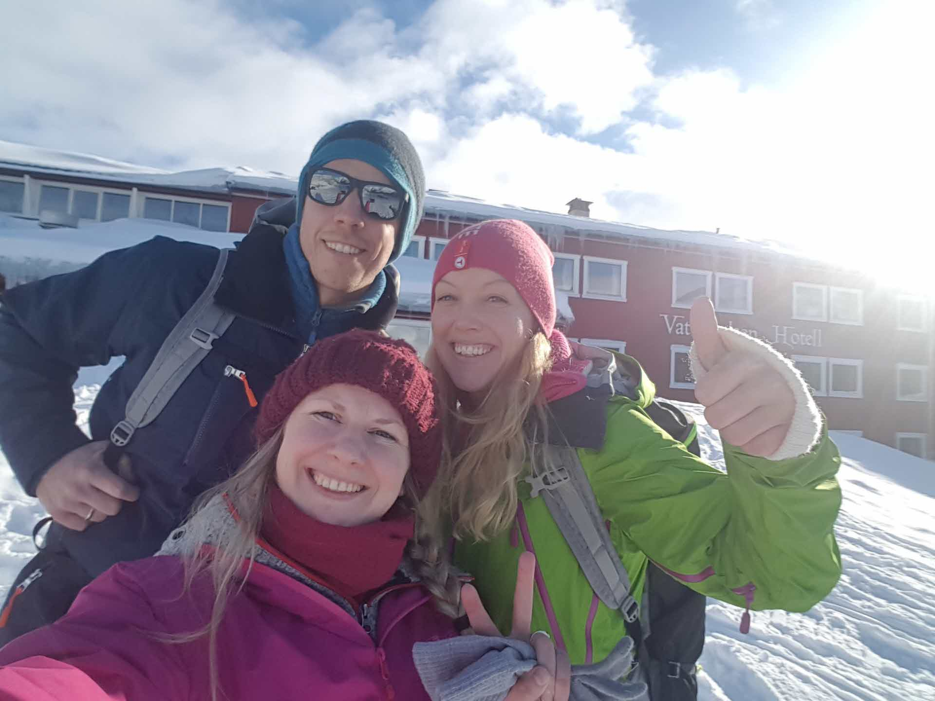Close up happy man and two women in winter clothing in front of Vatnahalsen Hotel on a sunny winter day