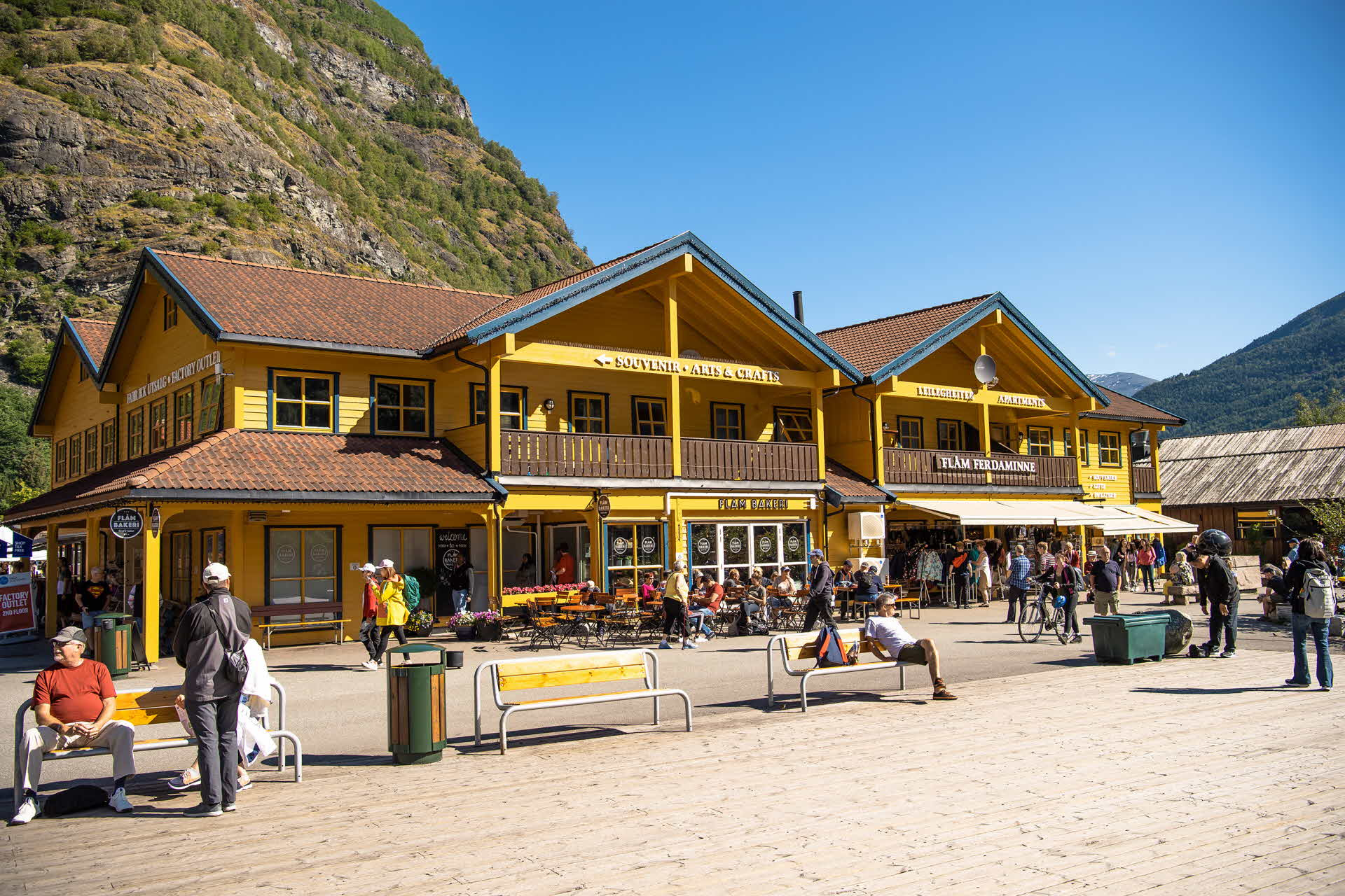 A summer day at the quayside in Flåm, with people sitting outside the Flåm Bakeri