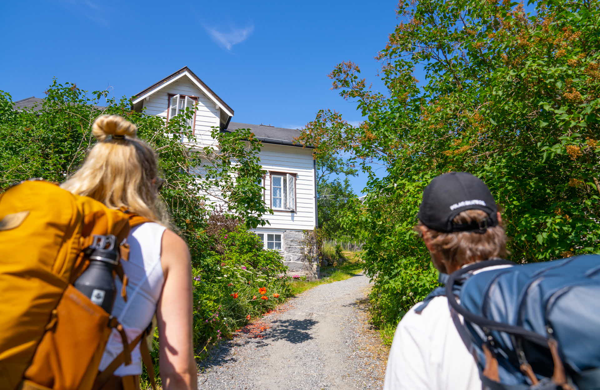 A man and a woman wearing backpacks looking at an old house in Geiranger