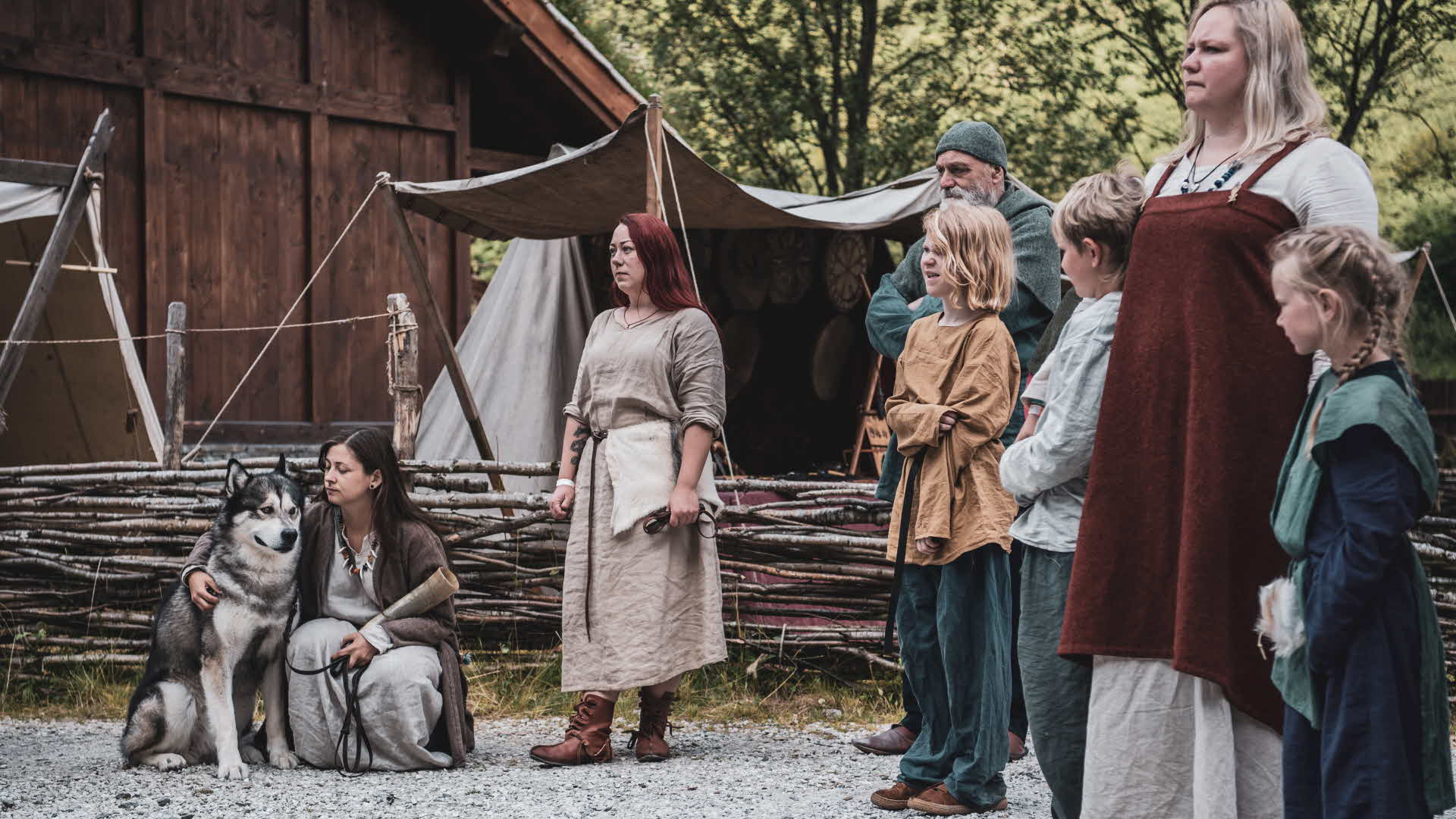 Viking Village in Gudvangen, group of family Viking and husky standing outside authentic building in traditional Viking wear