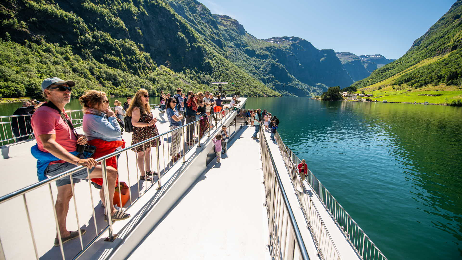 People standing outside by winding rails on board Future of The Fjords in UNESCO listed Nærøyfjord in summer