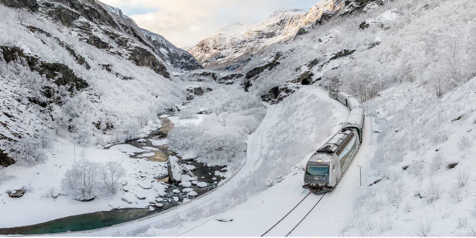 A train on its way down the Flåm Valley on a snowy winter day