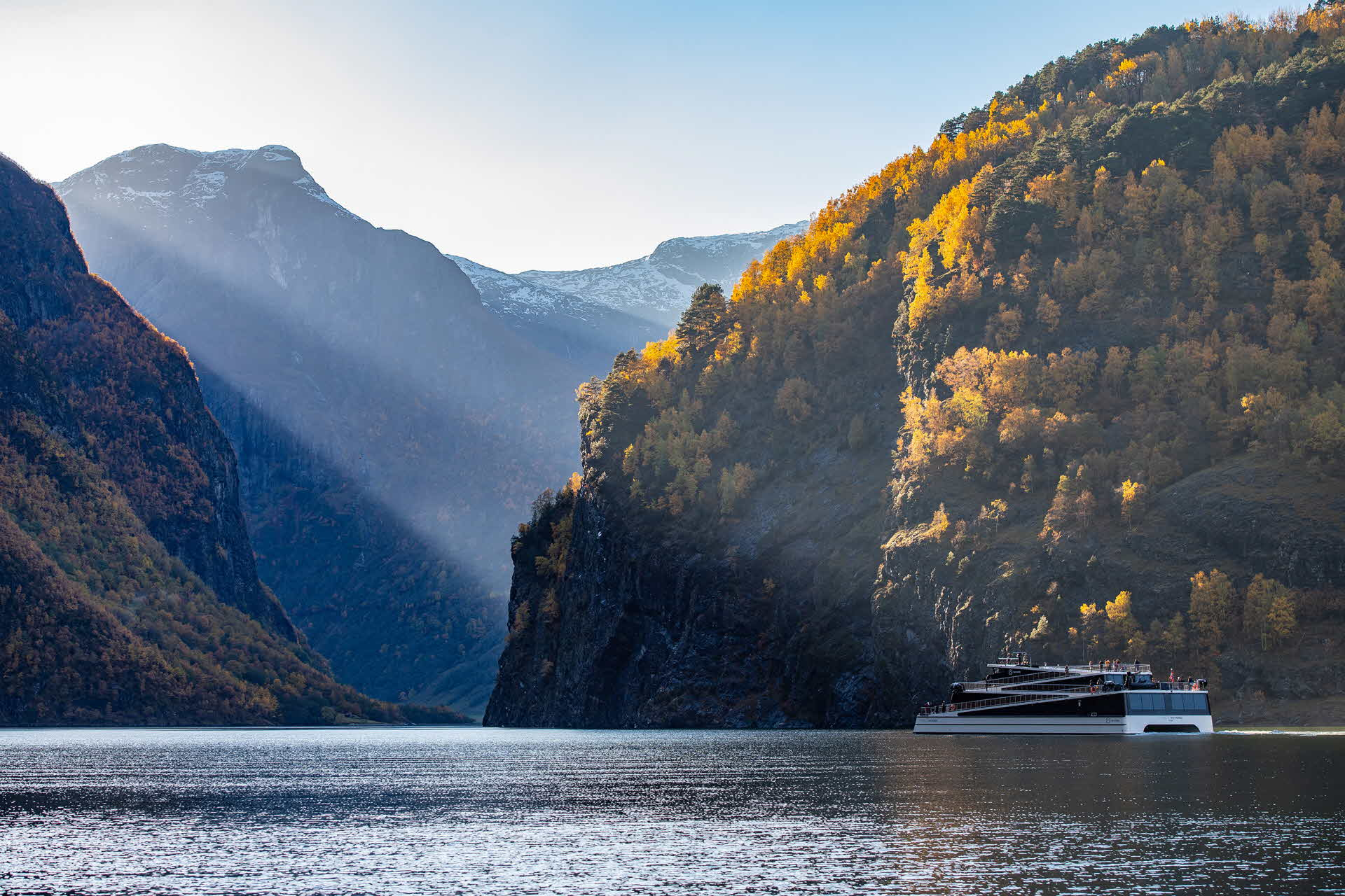 Panoramic view of woman standing on outside deck Vision of The Fjords overlooking the UNESCO listed Naeroyfjord in summer