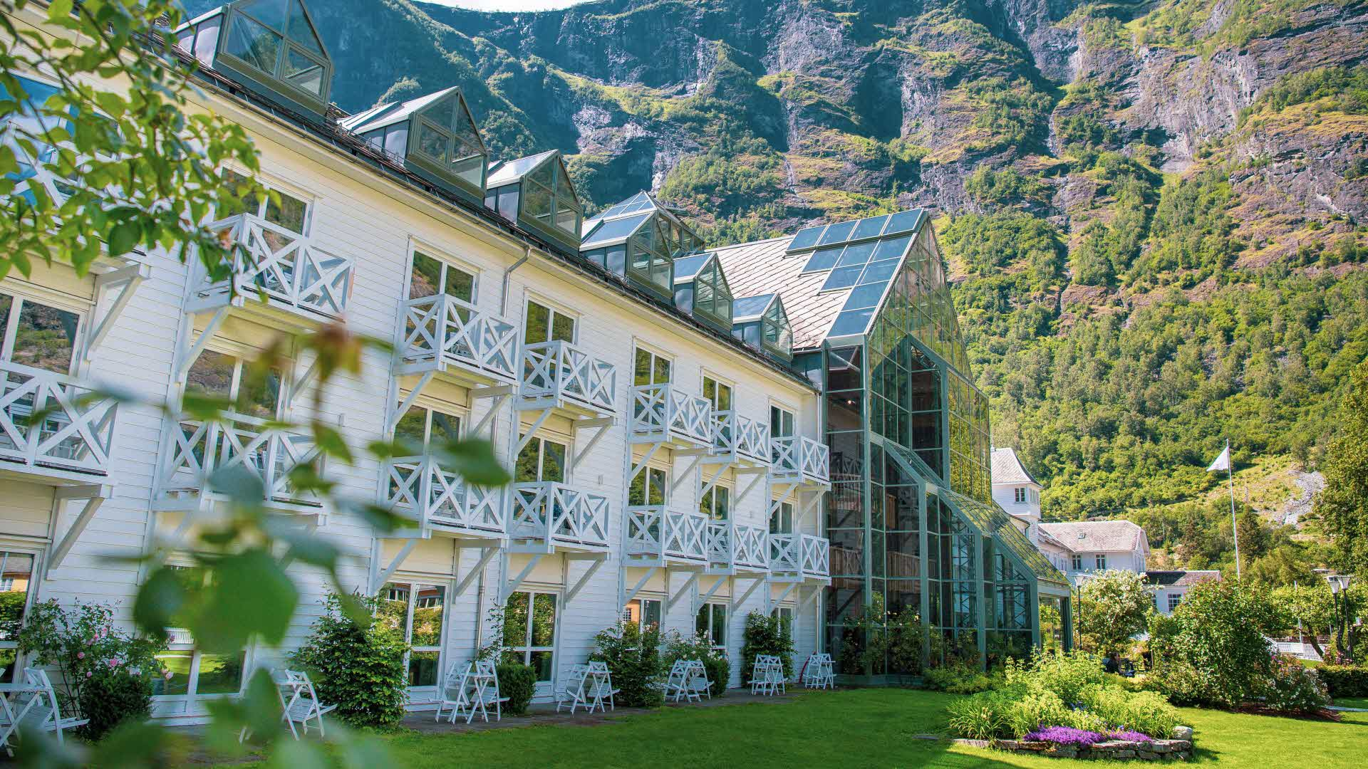 Fretheim Hotel seen from the garden in summer with leaves in front and steep mountains behind