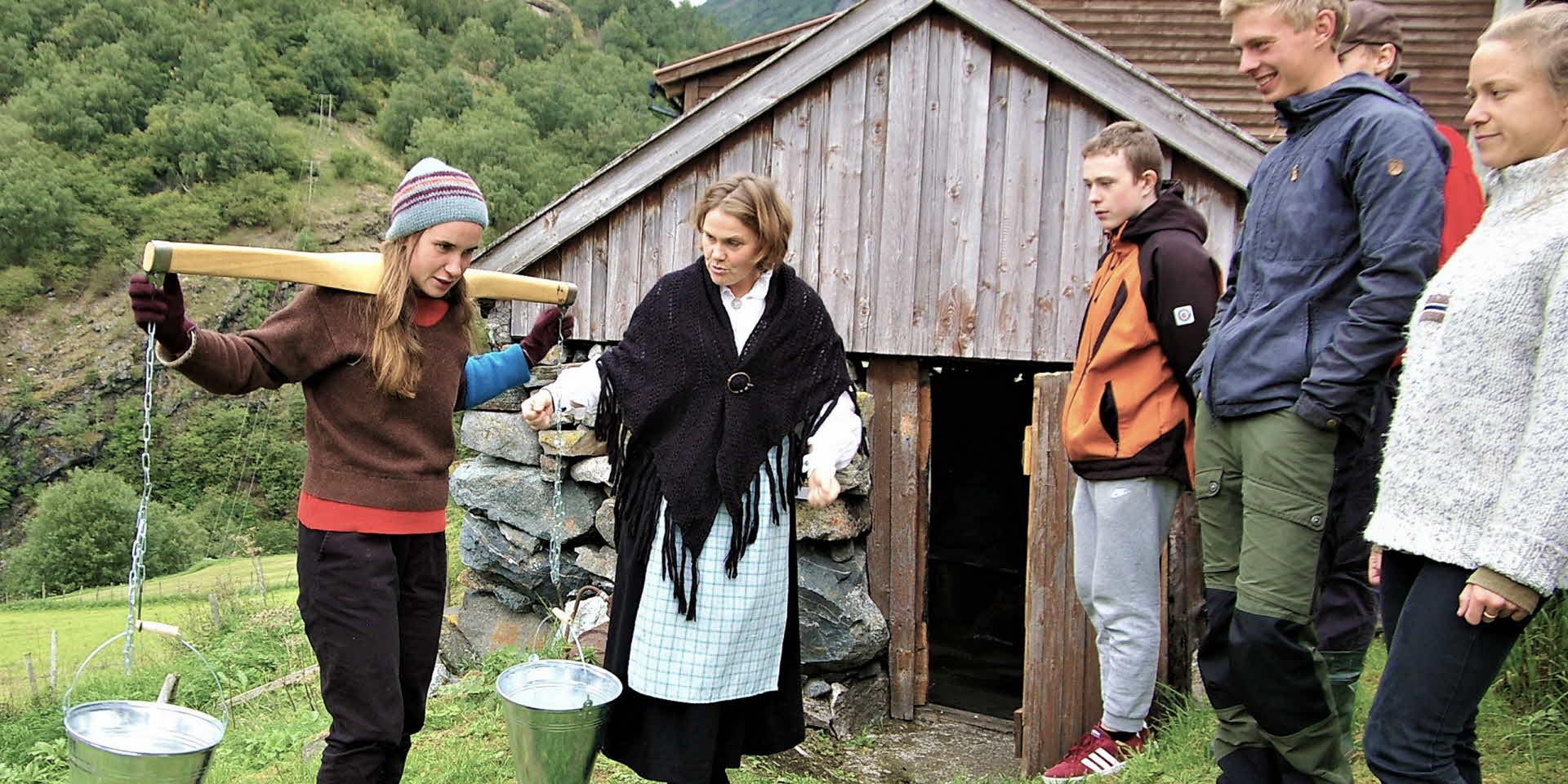 伝統的なドレスを着た農場の女性は、古いヤギ小屋の外で肩からぶら下がる2つのミルク桶を運ぶ方法を若者らに示しています