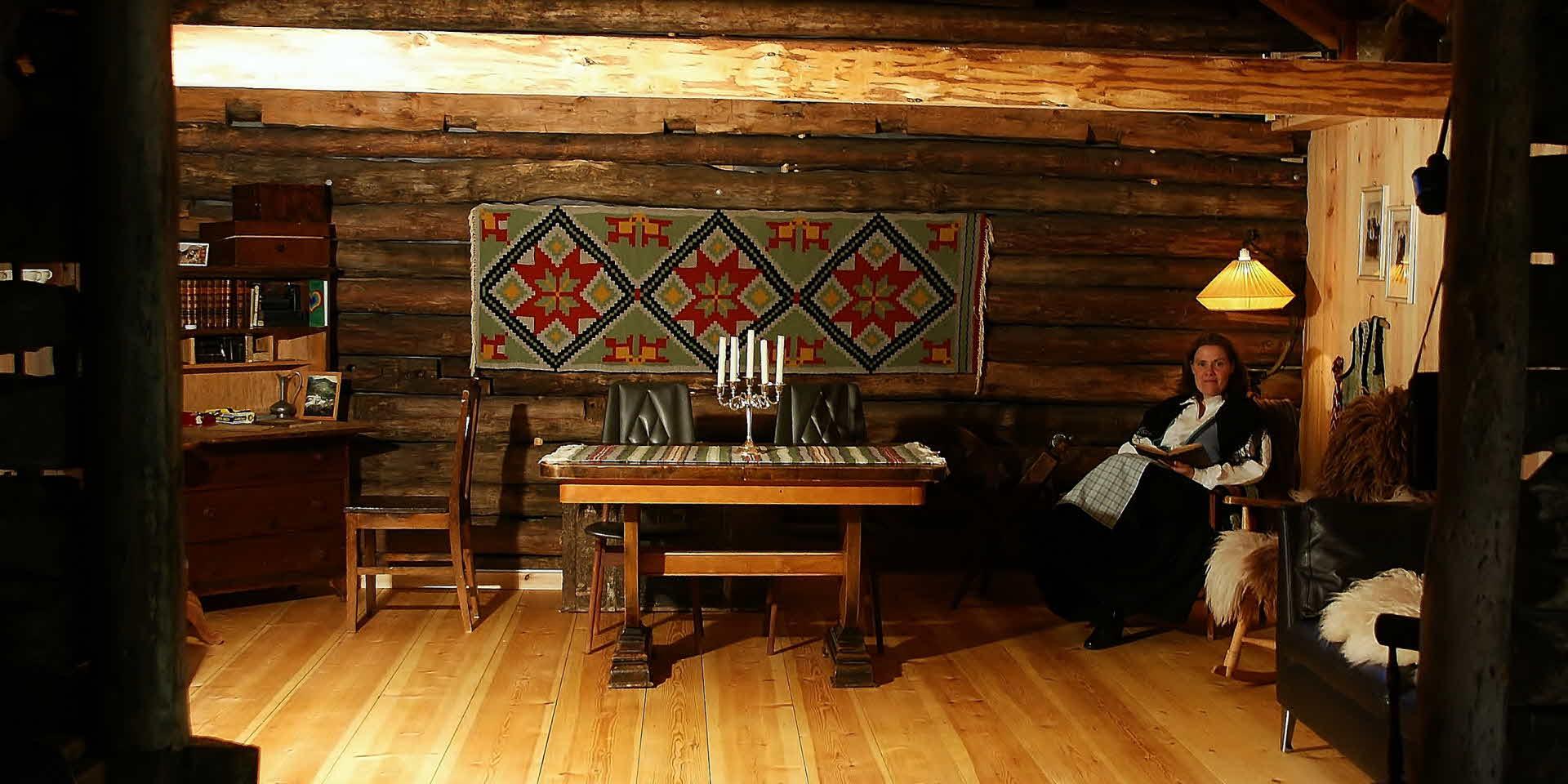 風変わりな木造の建物の中でアンティーク家具と壁にかかった大きな織絨毯に囲まれ、民族衣装のいでたちで座っている農場の女性。