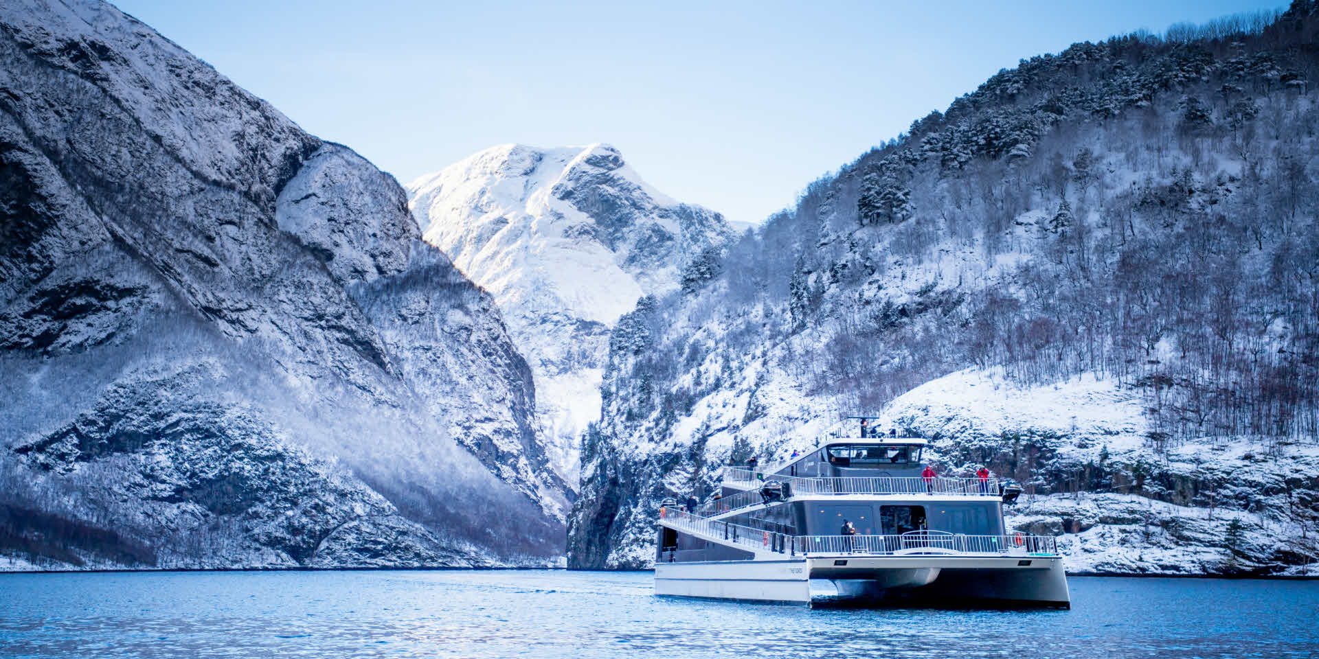 Electric tourist catamaran sailing on the Nærøyfjord surrounded by snow covered mountains.