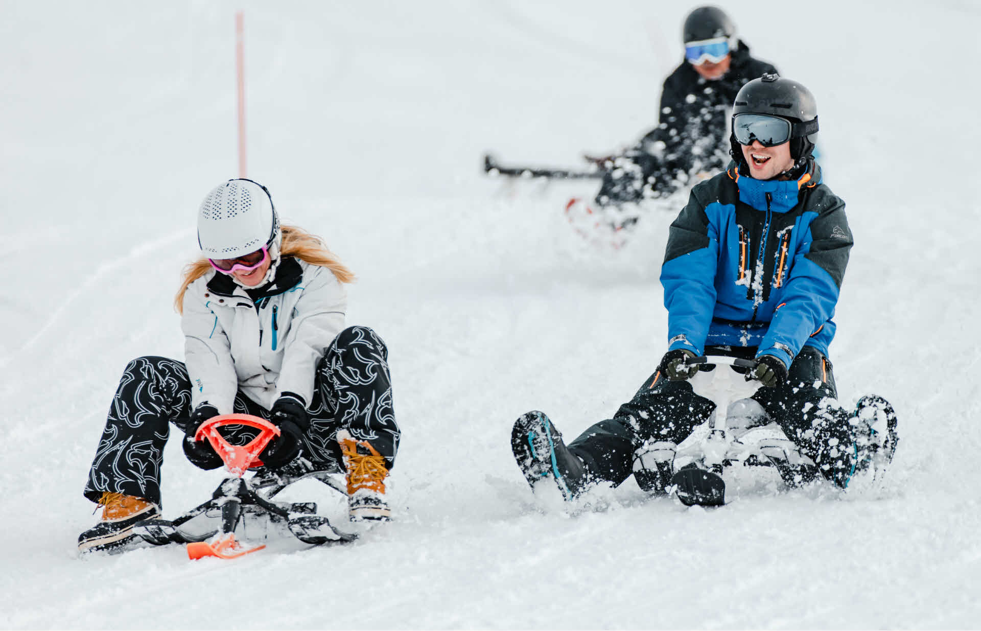 Three people sledging in the ski slopes in Myrkdalen