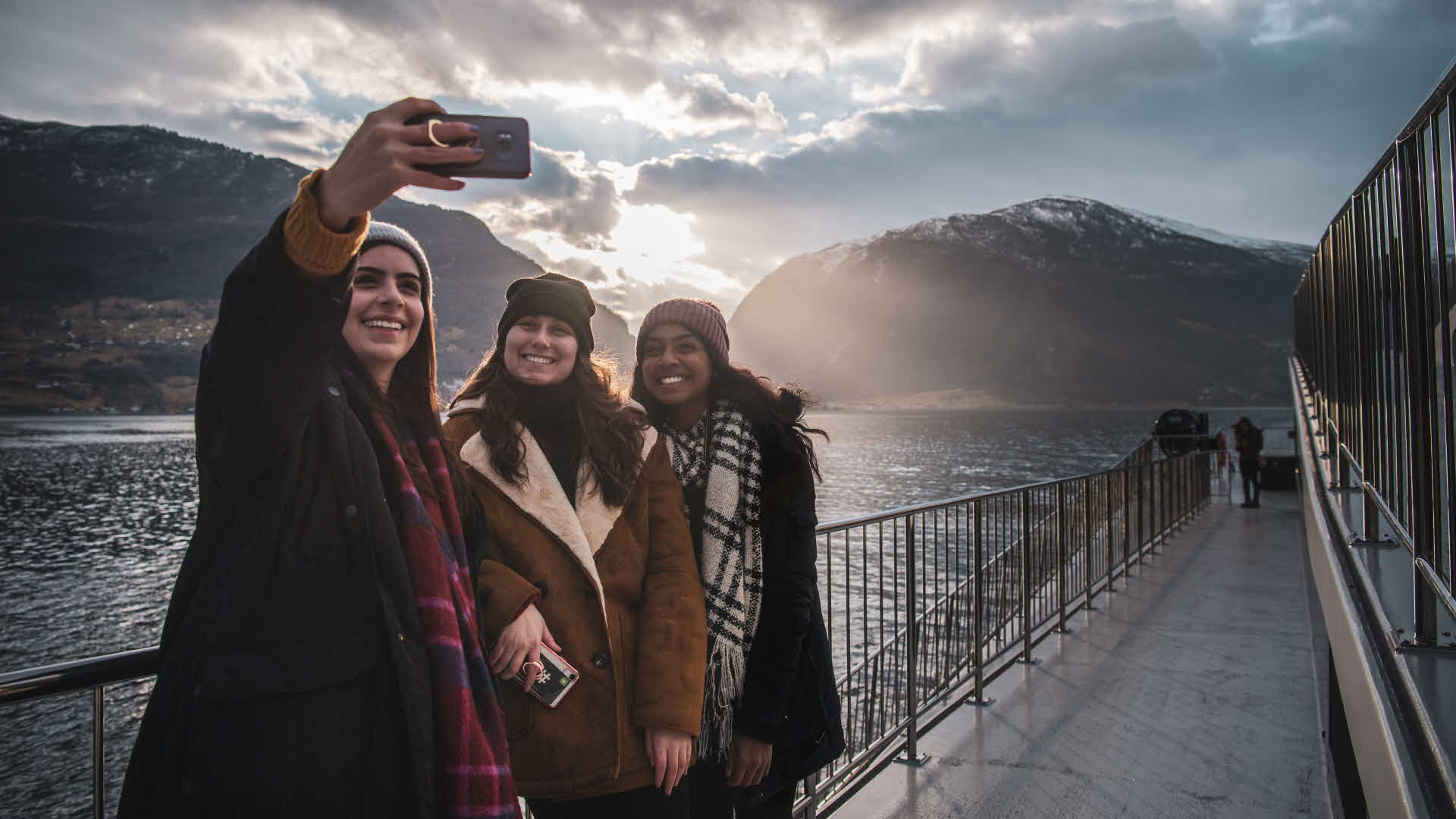 3 girlfriends on board Future of The Fjords in winter taking happy selfie as they sail through the Aurland fjord